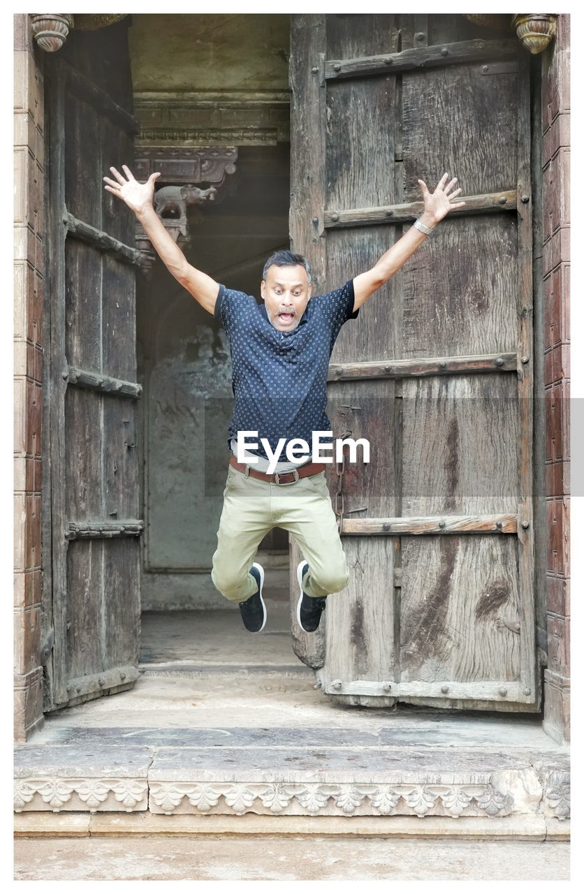 Full length of shocking man jumping with arms raised against door