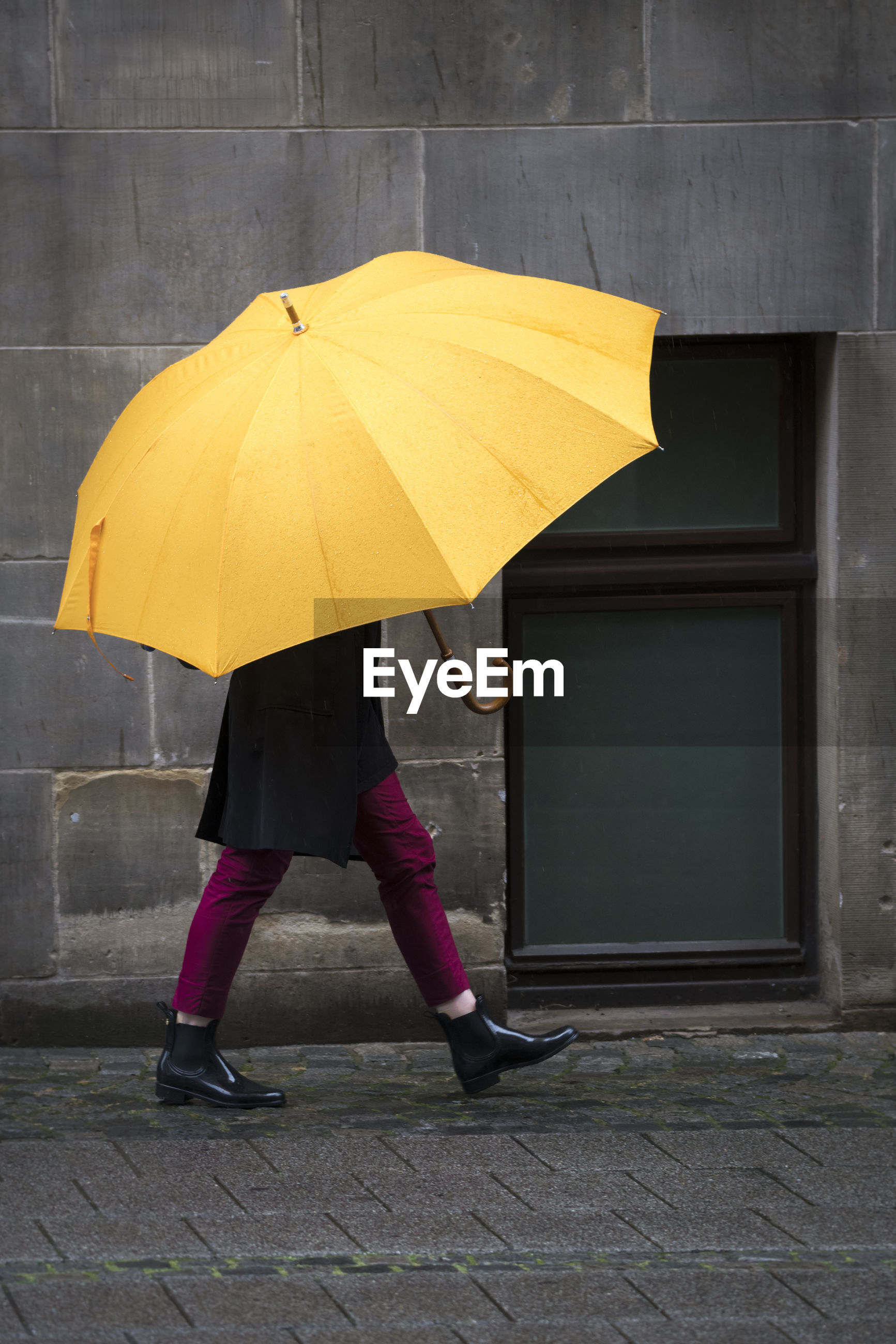 Low section of person carrying yellow umbrella on footpath during rain