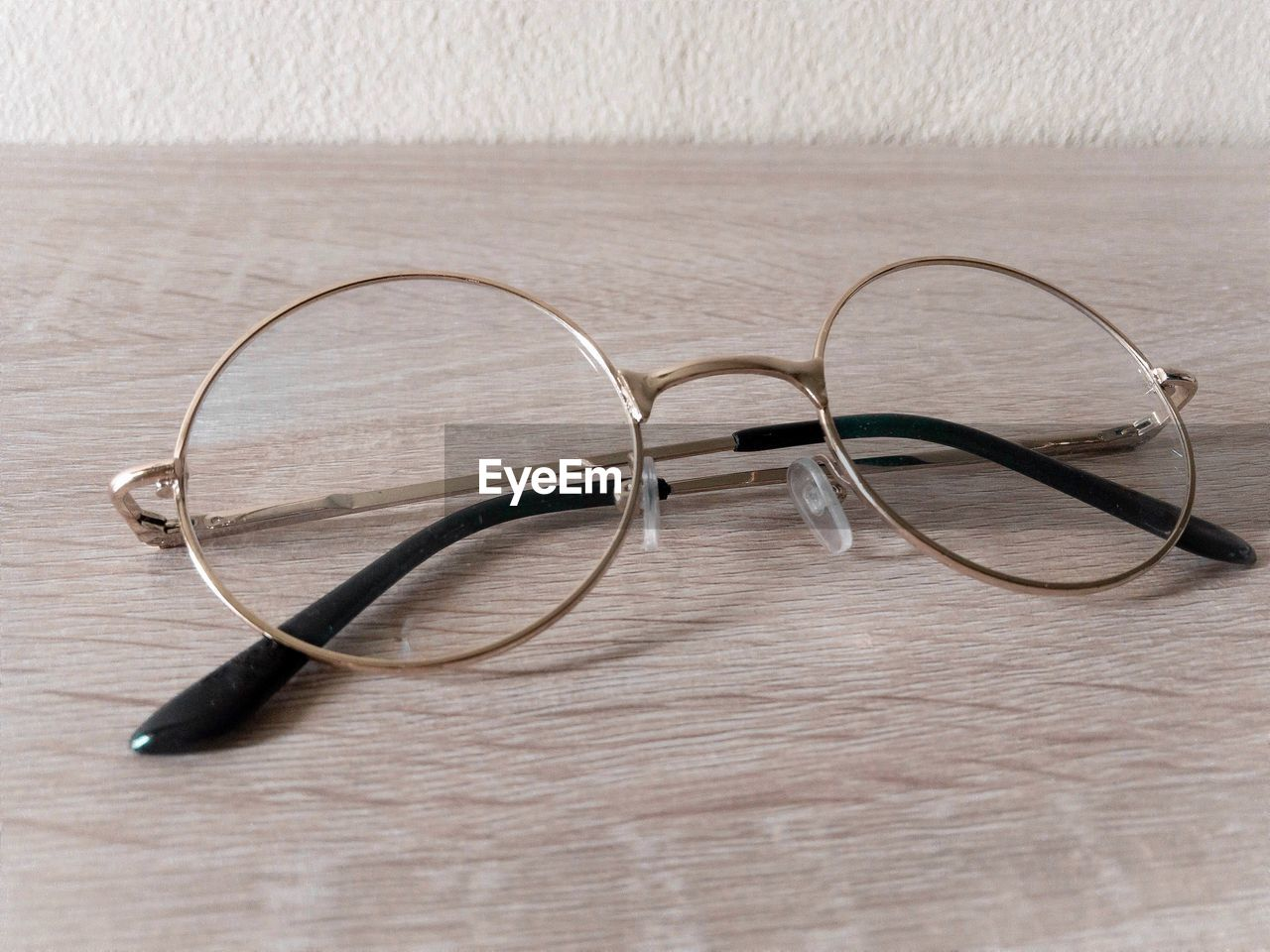 table, indoors, no people, glasses, wood - material, eyeglasses, still life, close-up, personal accessory, black color, high angle view, technology, connection, glass - material, transparent, single object, brown, wood, focus on foreground, white color, eyewear