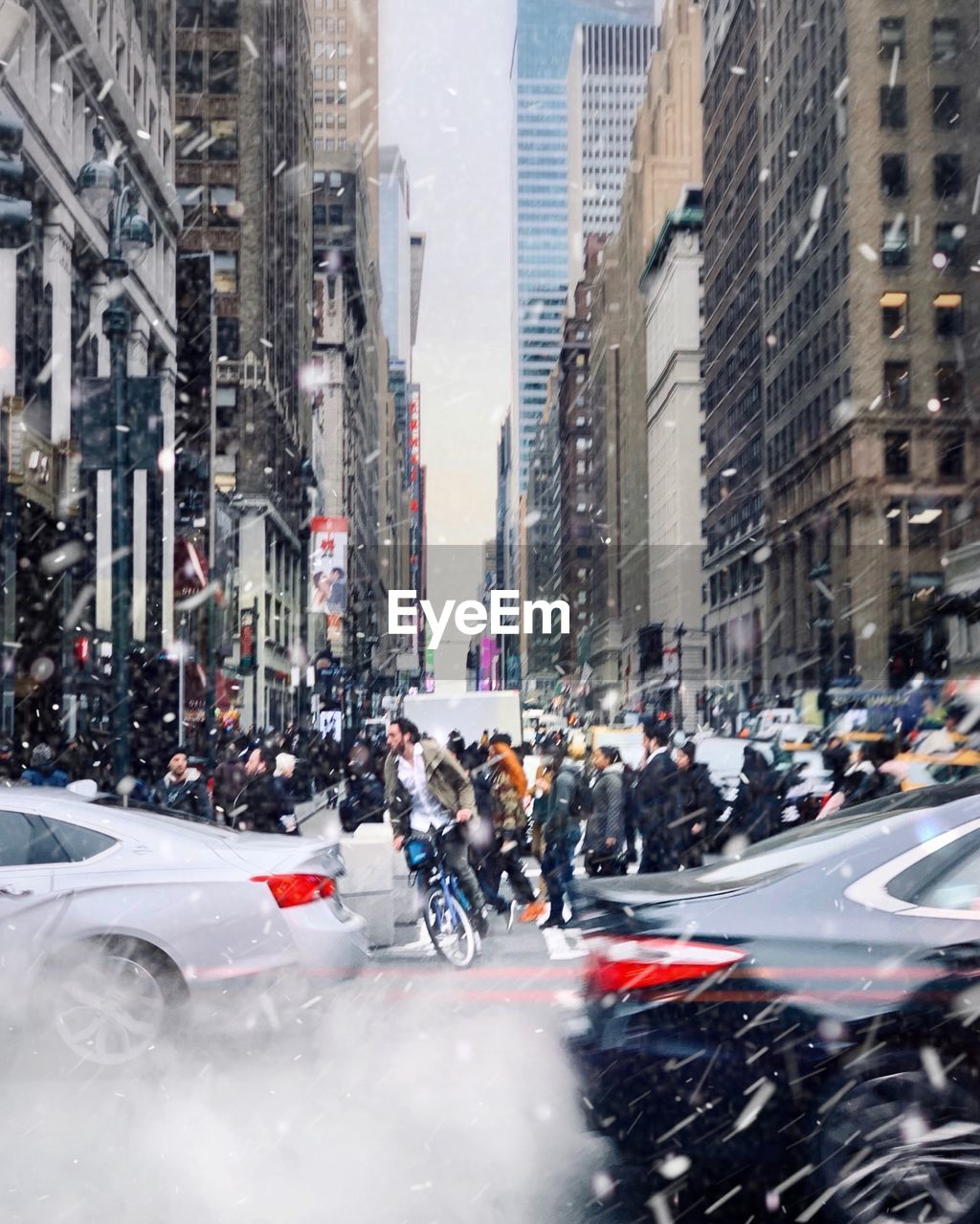 city, architecture, street, motion, transportation, car, building exterior, motor vehicle, mode of transportation, built structure, city life, traffic, on the move, blurred motion, road, crowd, people, city street, building, speed, outdoors, snowing, office building exterior, busy, skyscraper