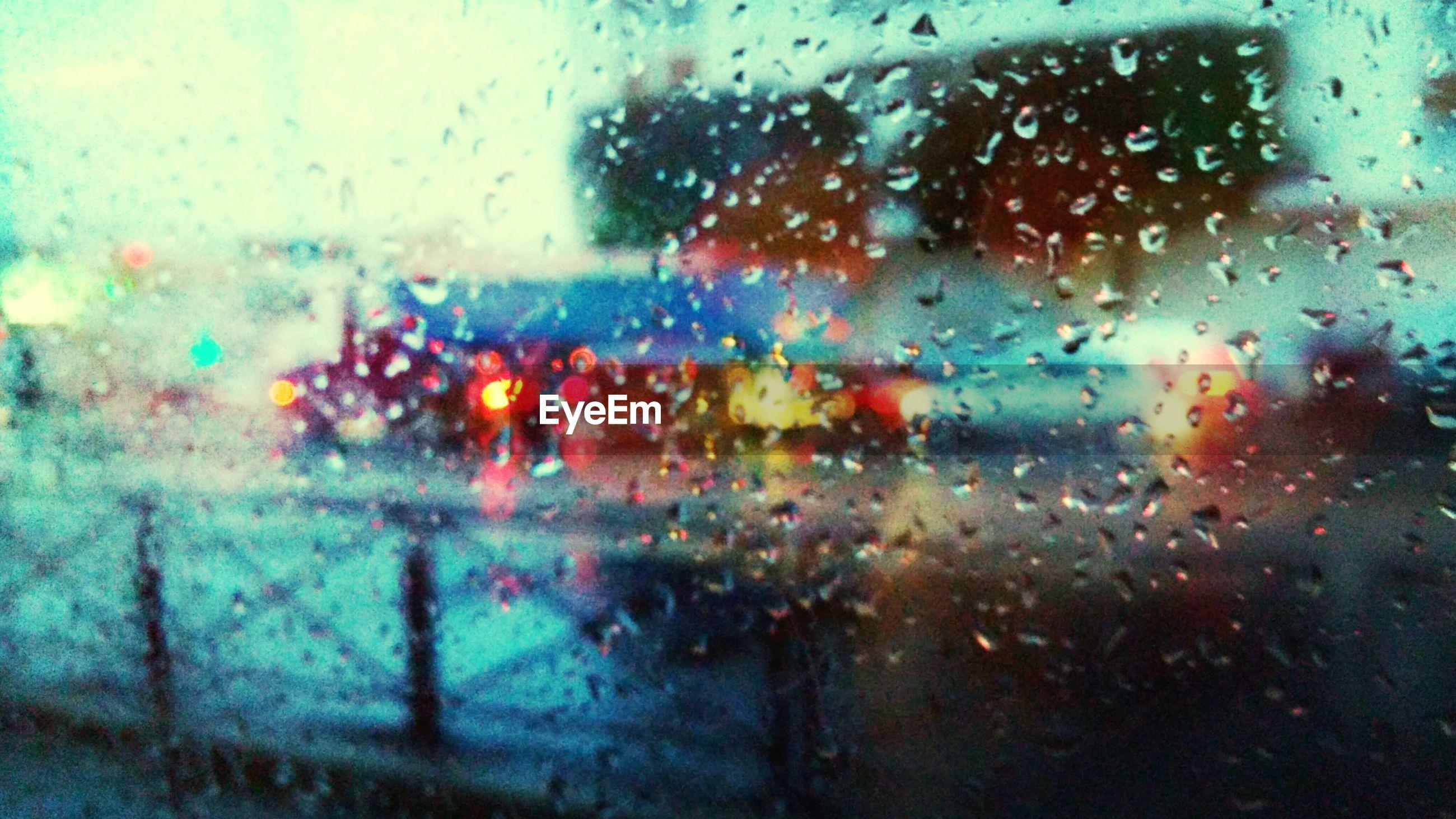 Full frame shot of wet glass against illuminated street