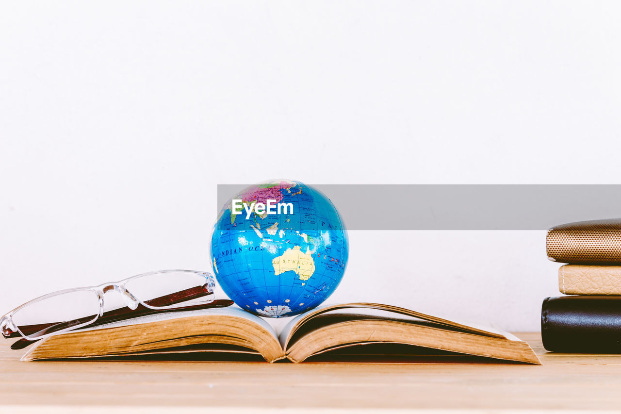 Close-up of book with globe and eyeglasses on table against white background