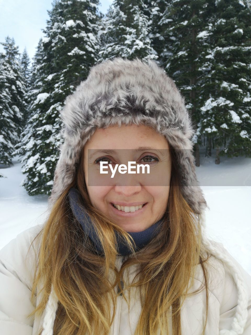 Portrait of smiling woman in snow against trees