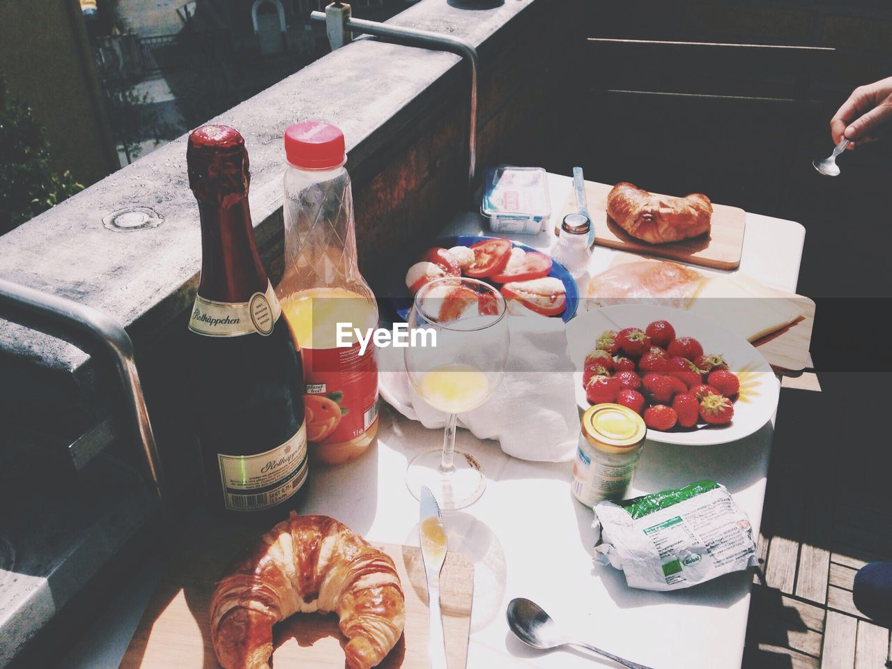 food and drink, human hand, food, drink, table, freshness, one person, refreshment, healthy eating, real people, croissant, fruit, breakfast, human body part, indoors, day, ready-to-eat, people
