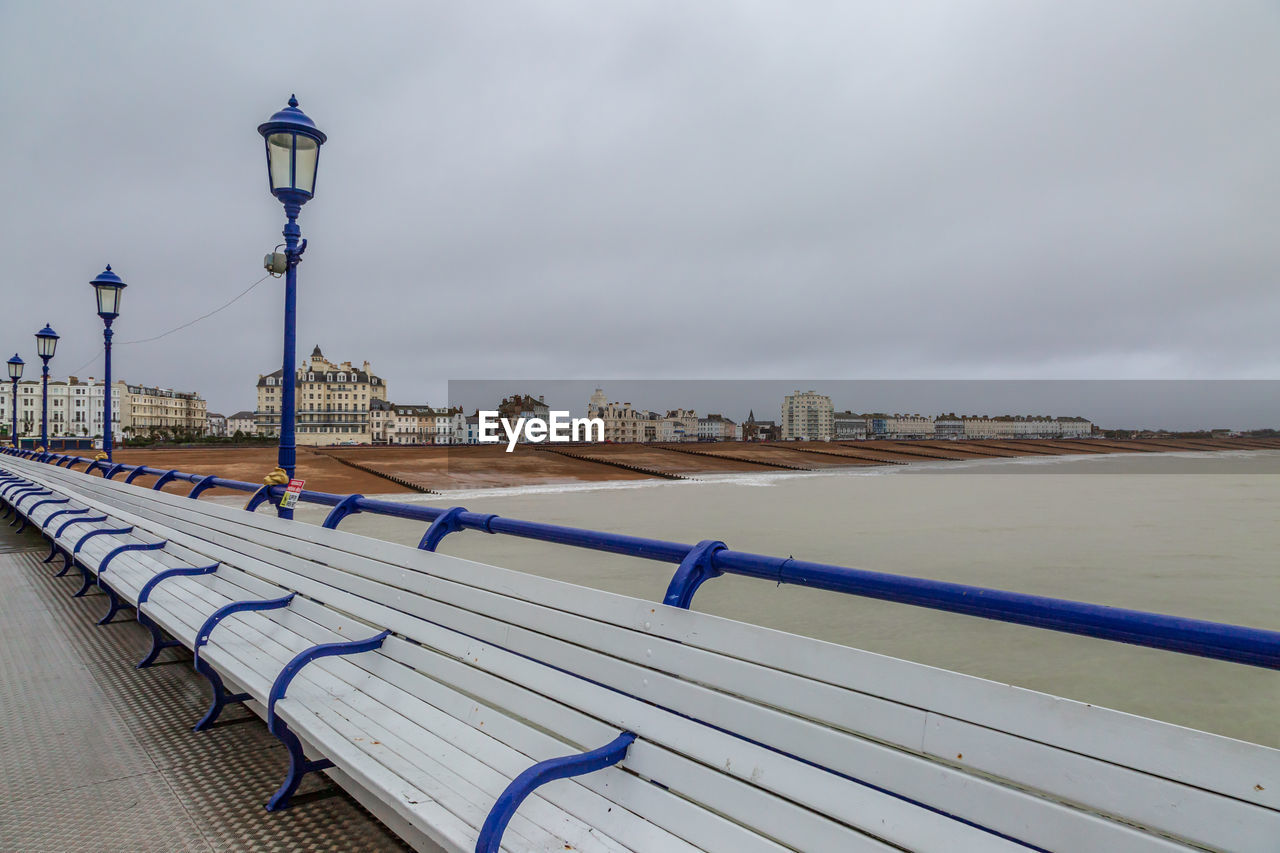 sky, water, lighting equipment, street light, architecture, built structure, nature, railing, building exterior, no people, cloud - sky, day, street, sea, bench, outdoors, city, seat, transportation, promenade