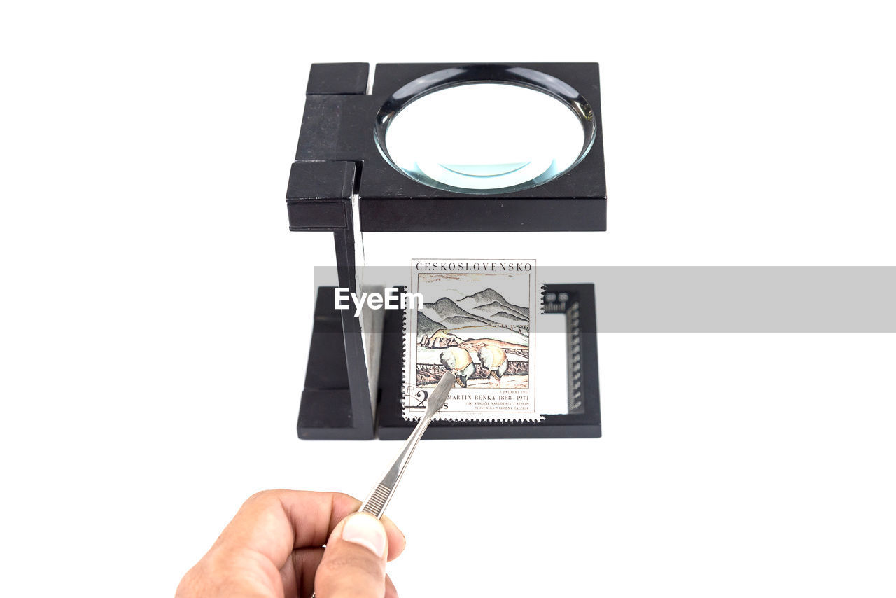 Cropped Hand Holding Postal Stamp Under Magnifying Glass With Tweezers On White Background