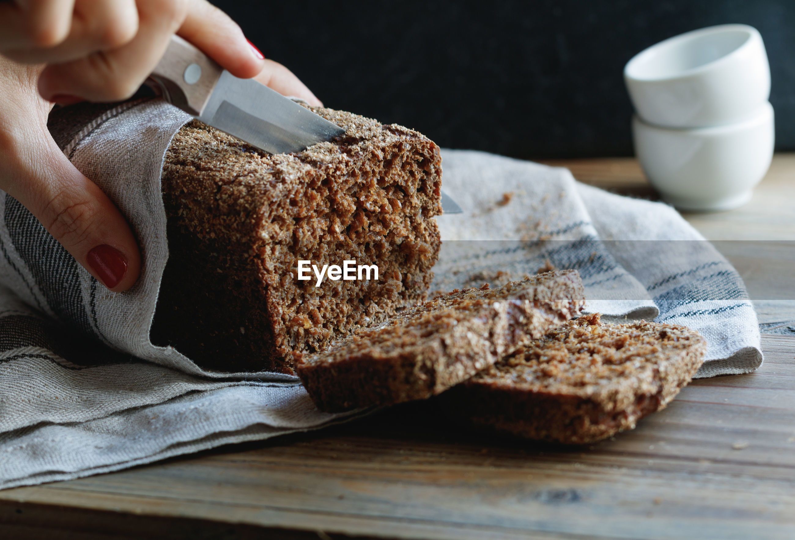 Cropped hand of woman cutting brown bread from knife