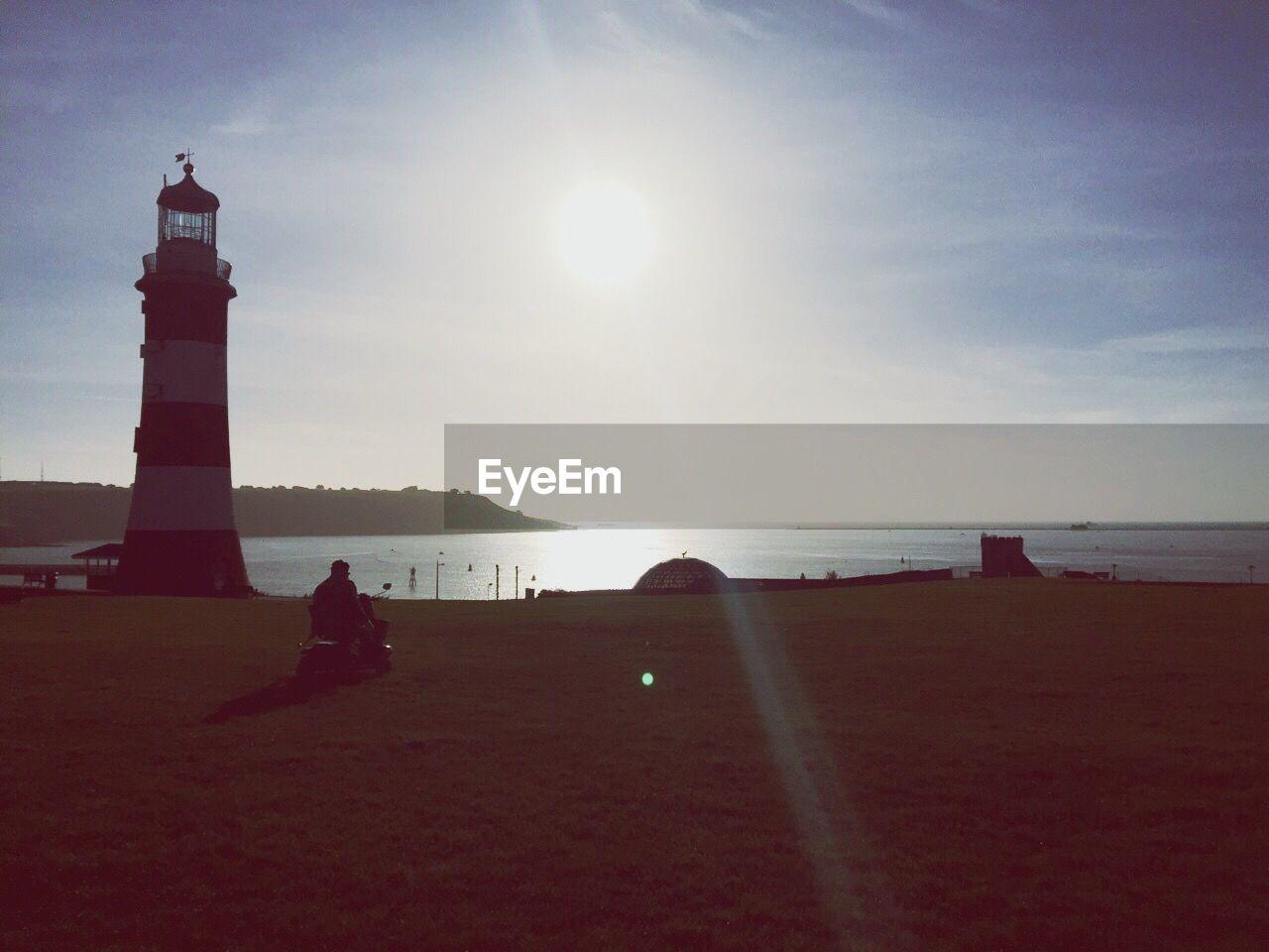 Silhouette Lighthouse Against Calm Sea