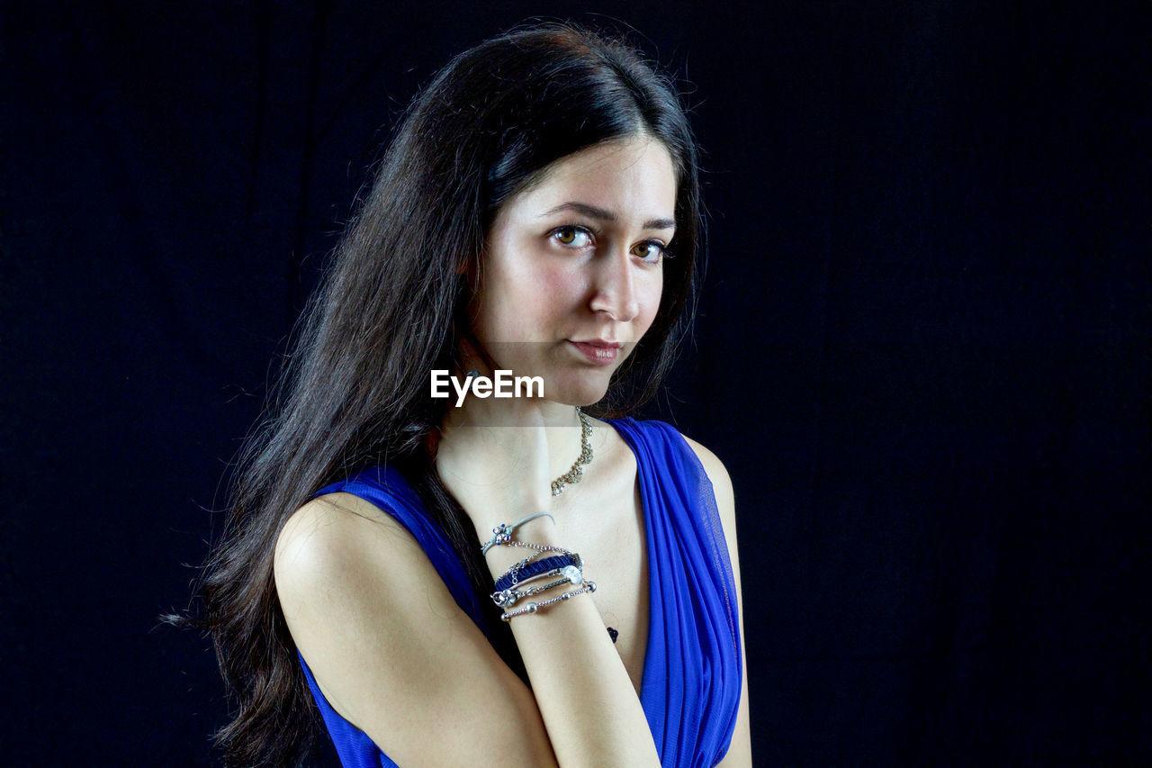 Portrait of beautiful female model in blue dress against black background