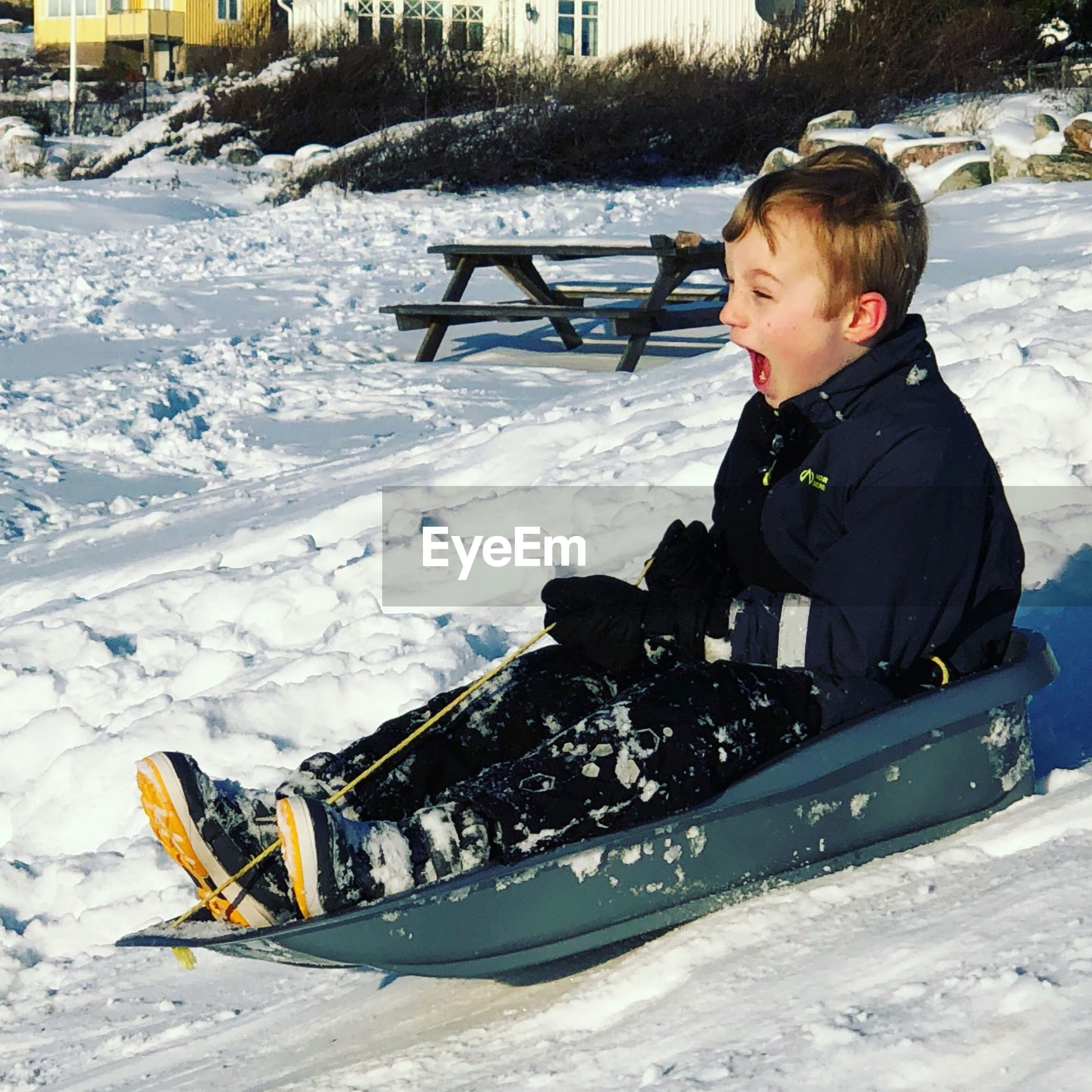 Cute boy with mouth open sitting on sled during winter