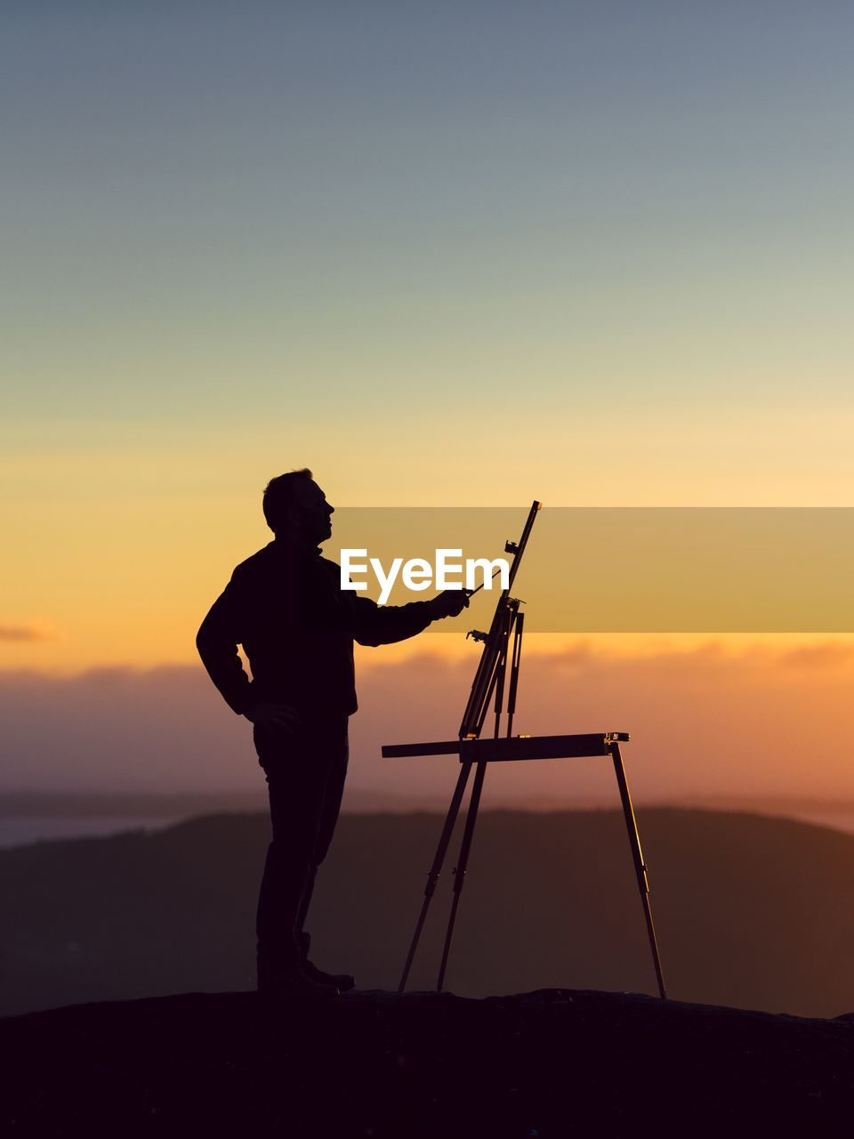 Silhouette man painting while standing against sky during sunset