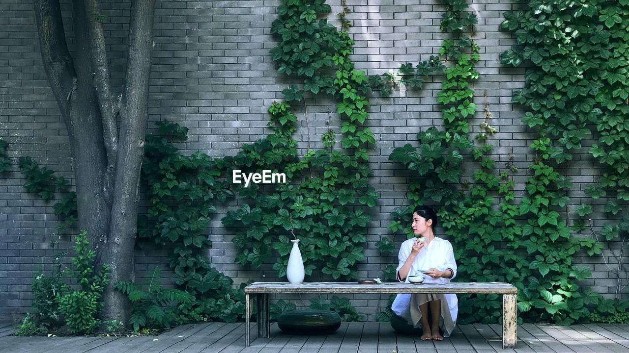 Portrait Of Smiling Woman Sitting Against Plants