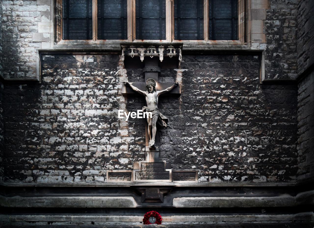Jesus statue mounted on stone wall