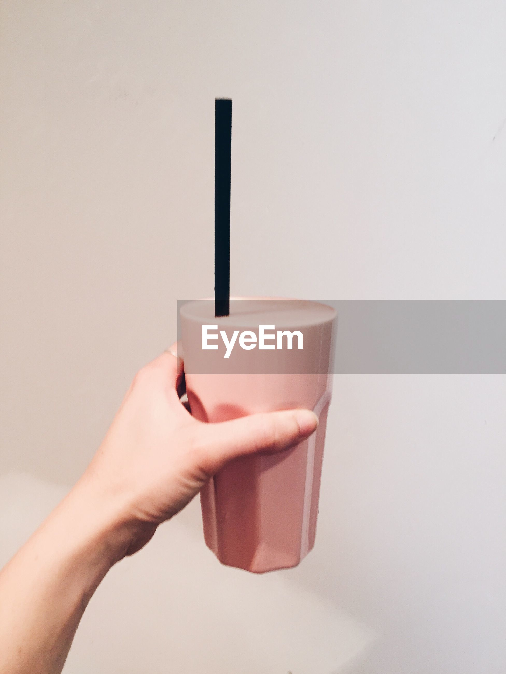 Cropped hand holding glass of smoothie against white background