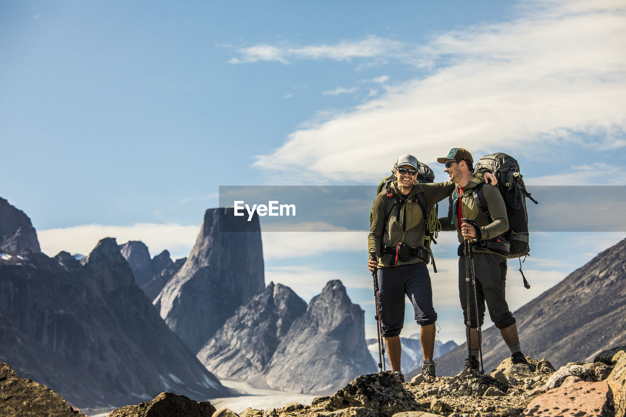 PEOPLE STANDING ON MOUNTAINS AGAINST SKY