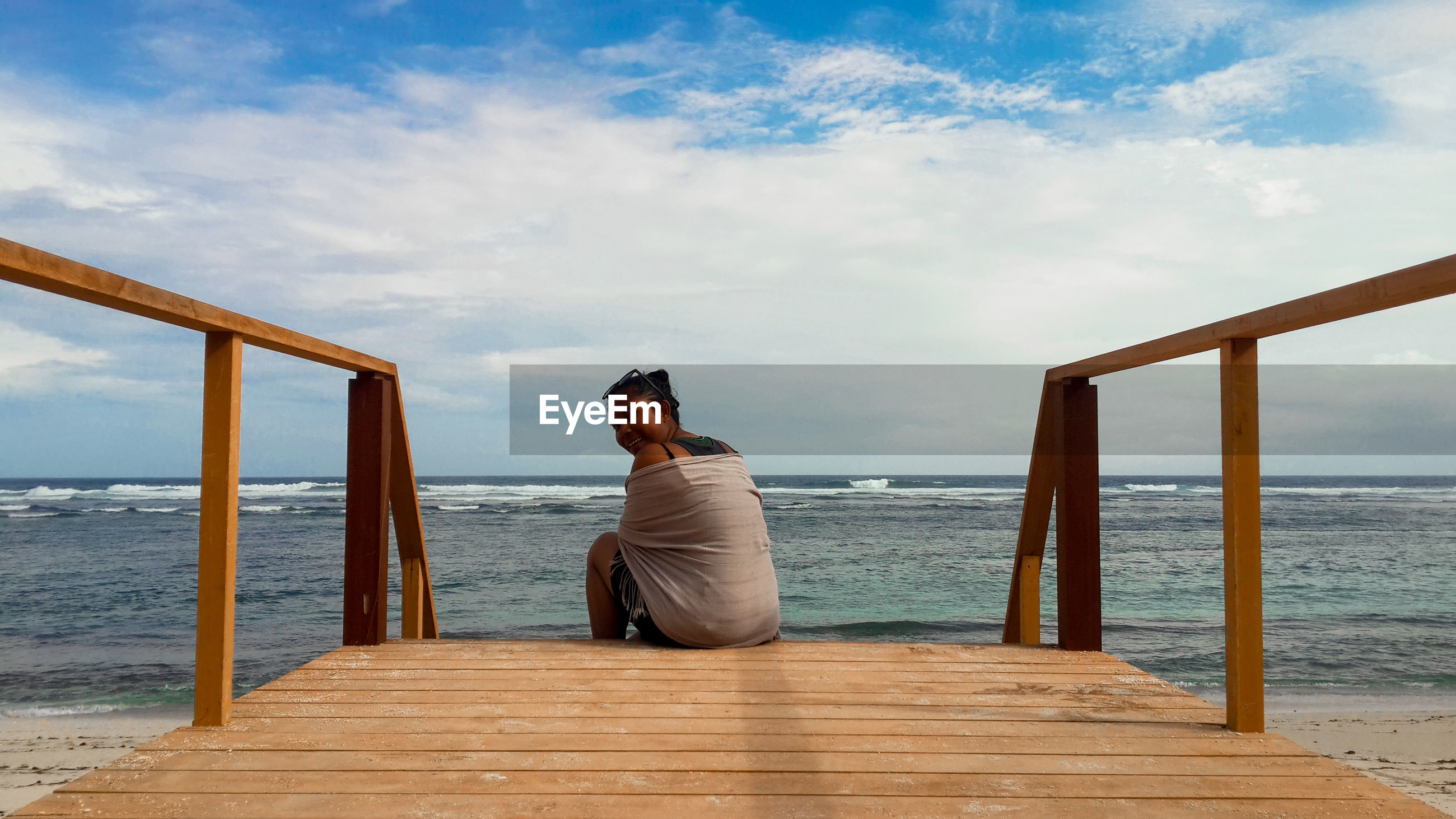 Woman sitting on wooden pier looking at sea against sky