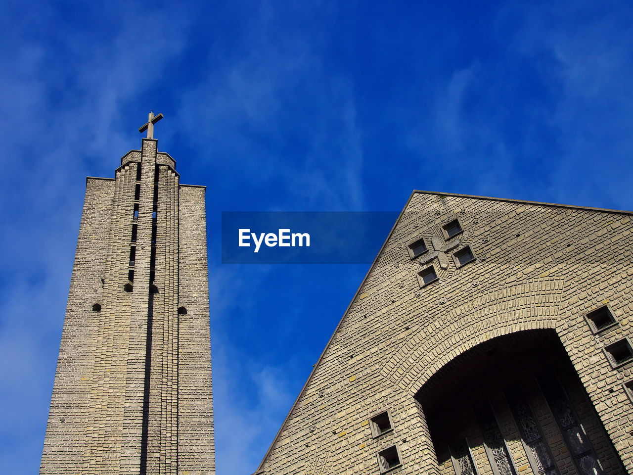 Low angle view of church against blue sky on sunny day