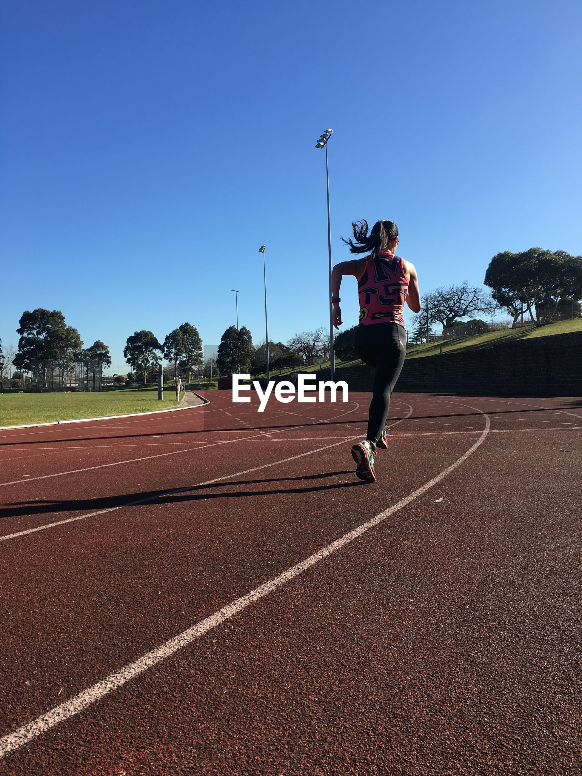 Rear view of woman running in sports track against clear blue sky