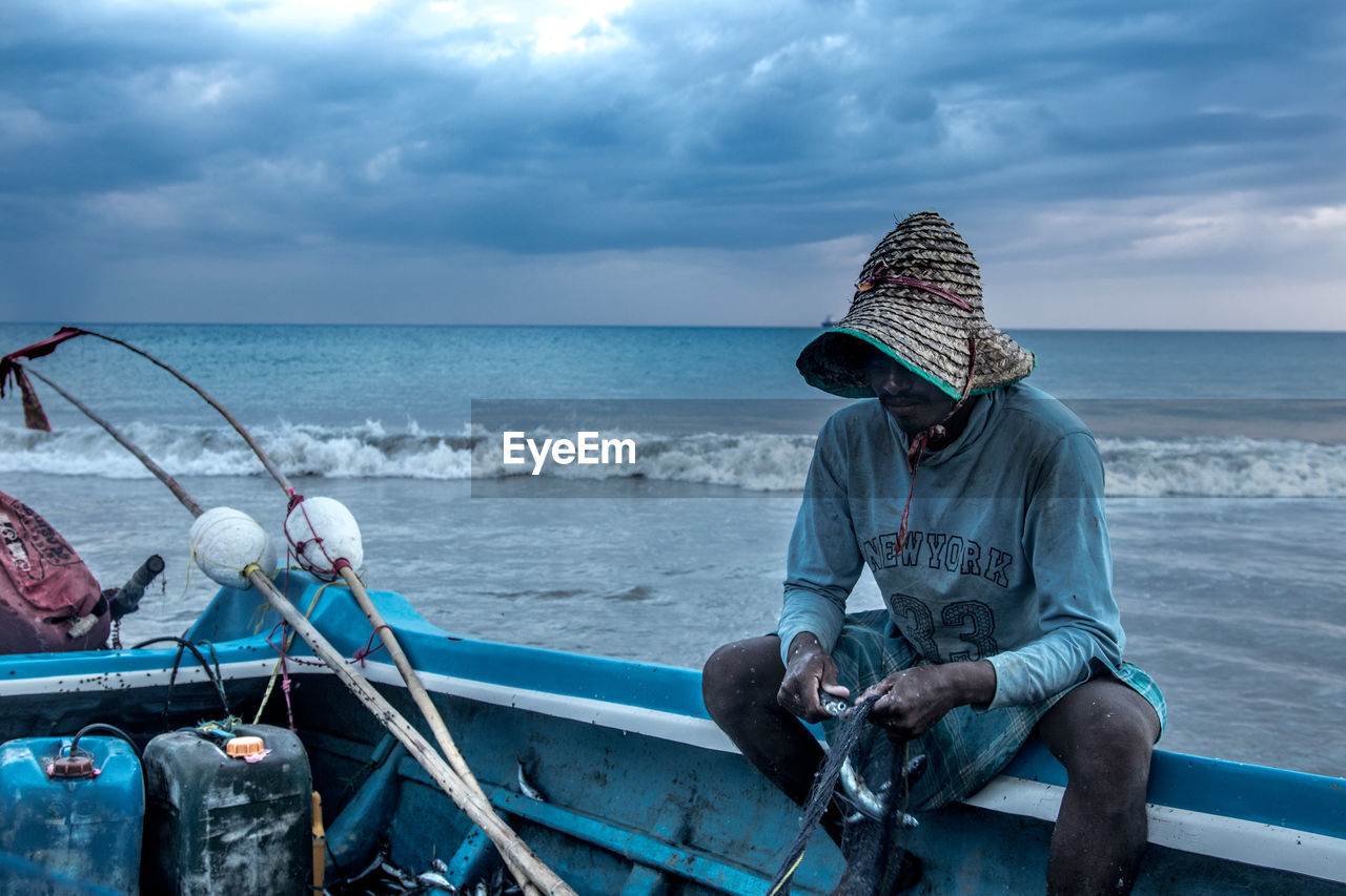 sea, water, sitting, horizon over water, real people, cloud - sky, horizon, sky, nautical vessel, one person, transportation, mode of transportation, beauty in nature, nature, scenics - nature, casual clothing, leisure activity, men, outdoors