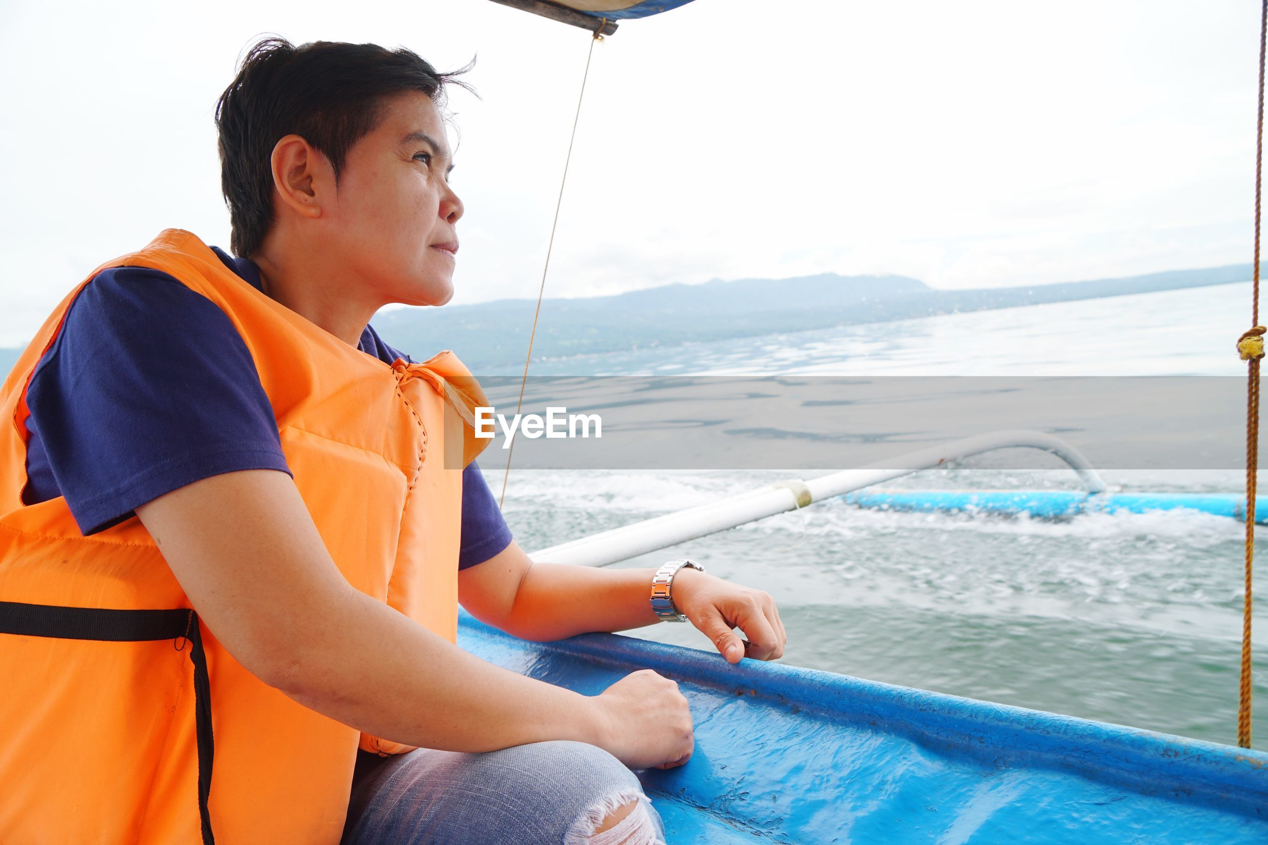 Side view of mature woman looking away while sitting in boat on sea against sky