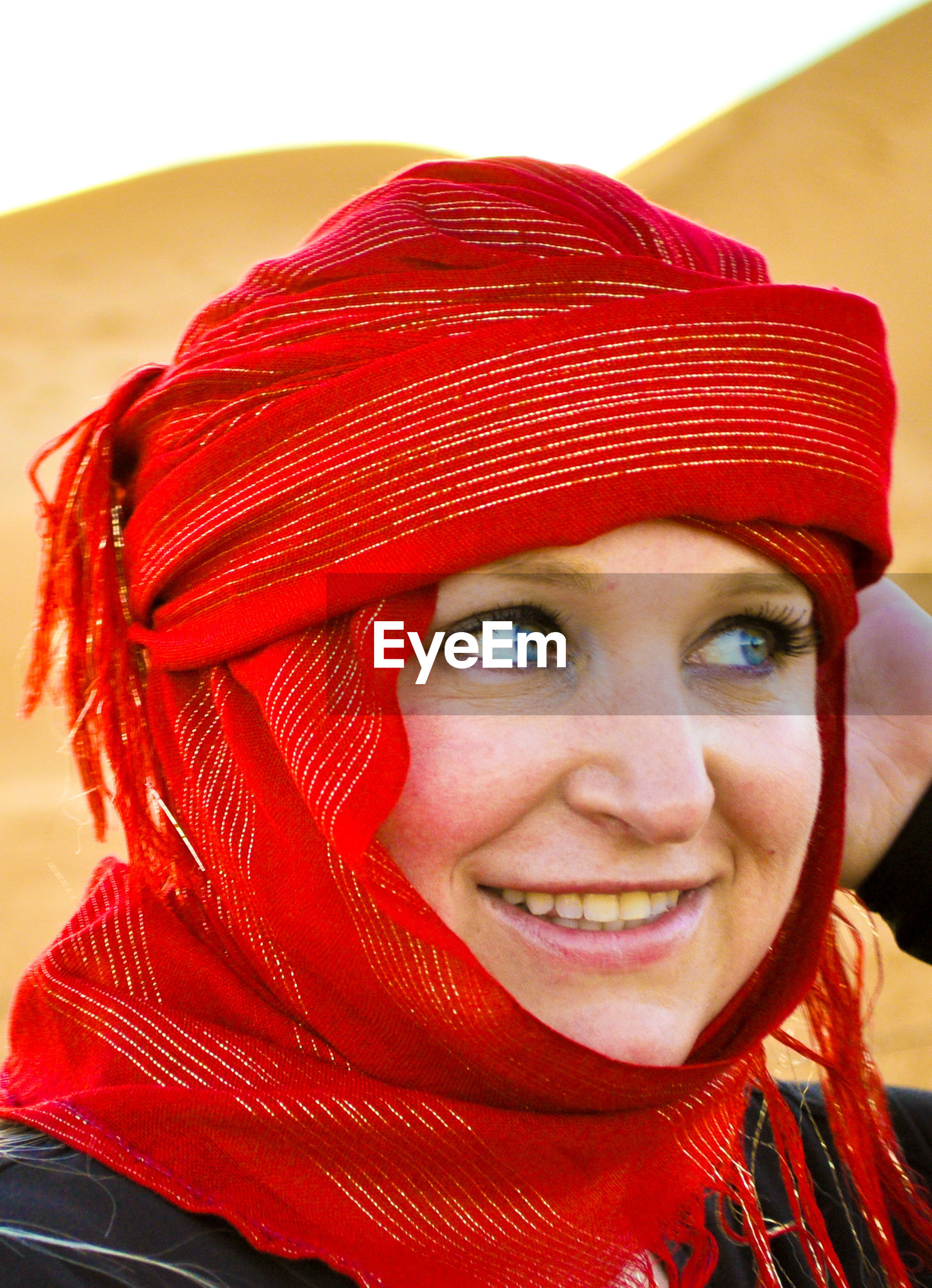 Close-up of smiling woman wearing red headscarf at desert