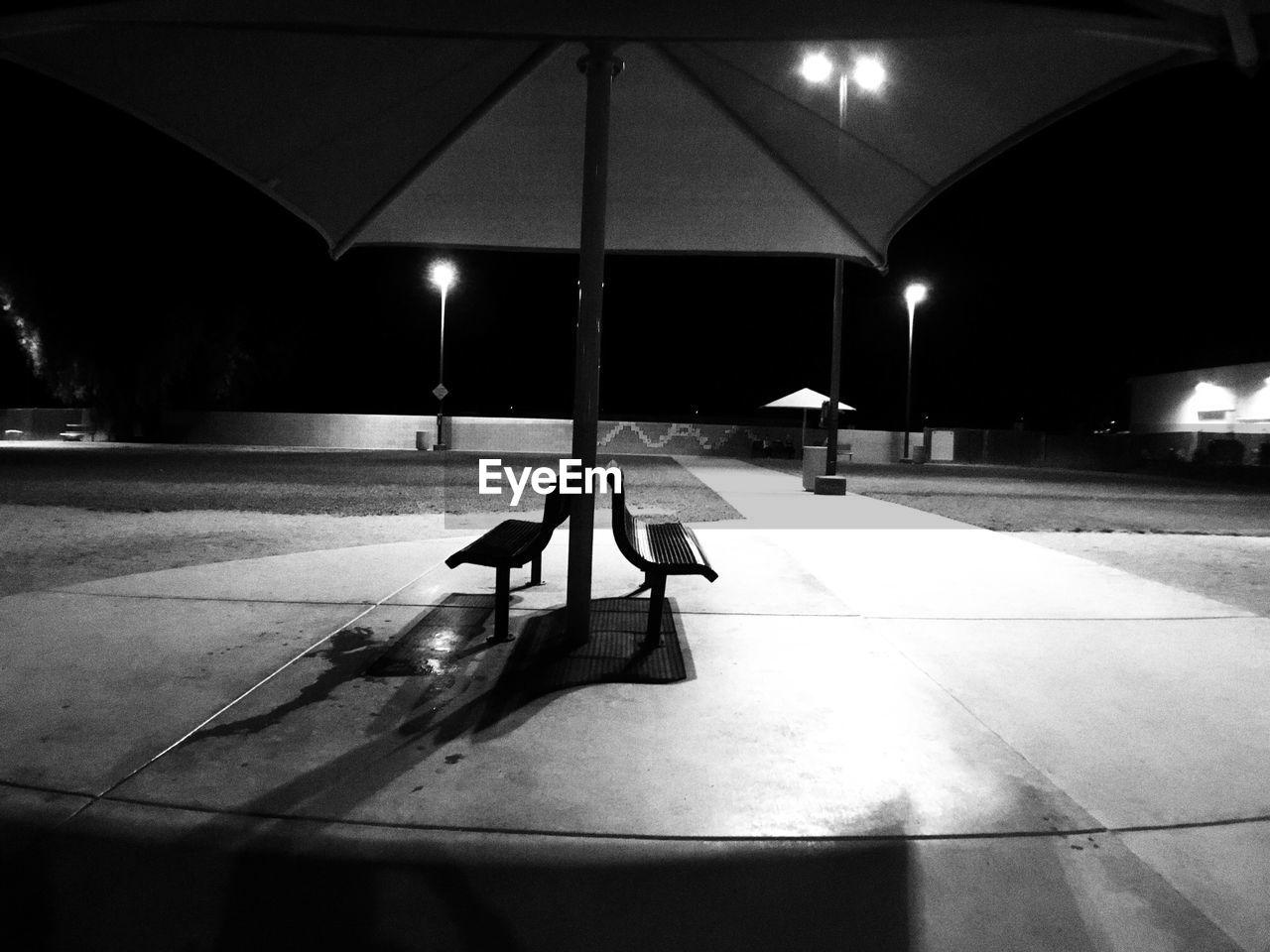 Illuminated empty benches in park at night
