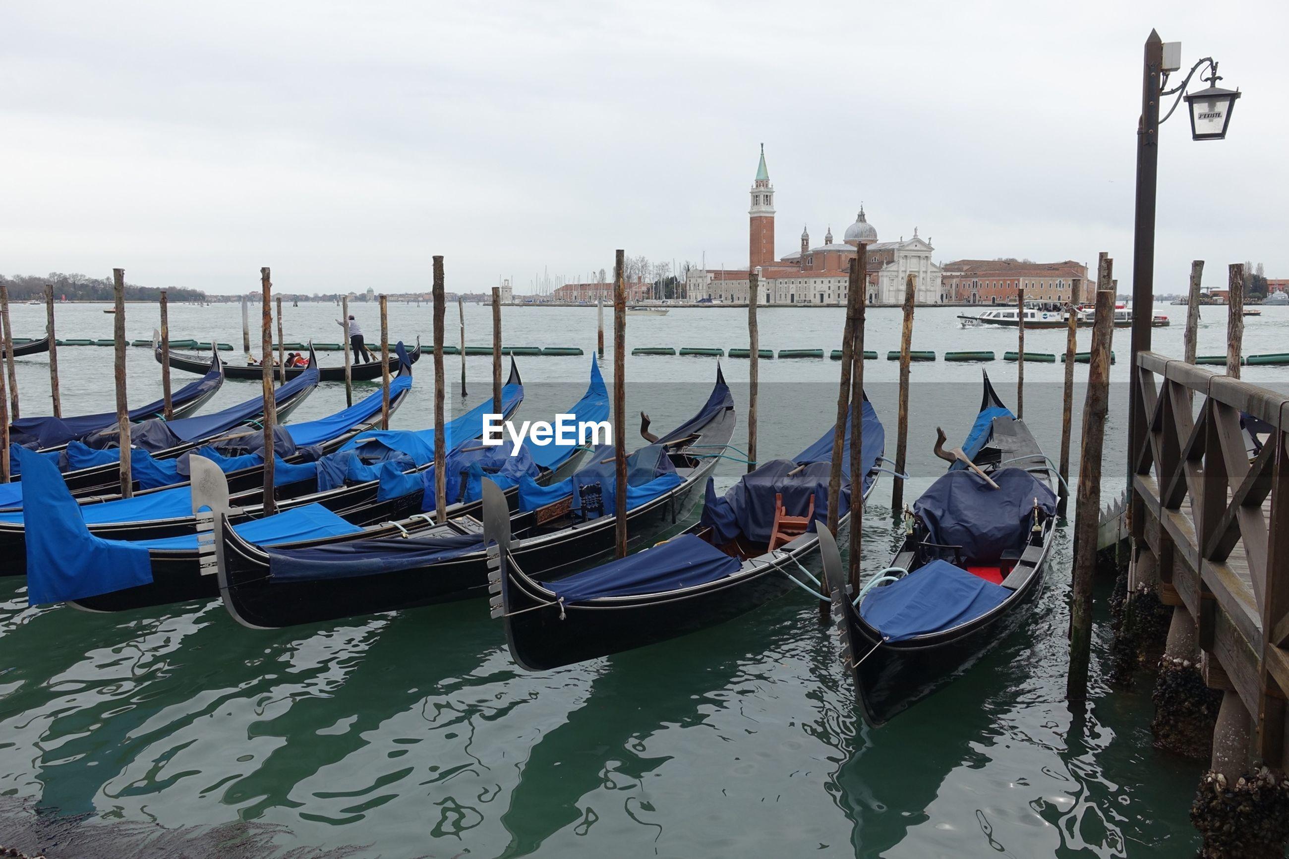 Gondolas moored on grand canal against clear sky