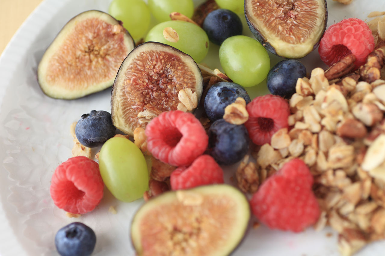 Close-up of fruits and figs with granola in plate