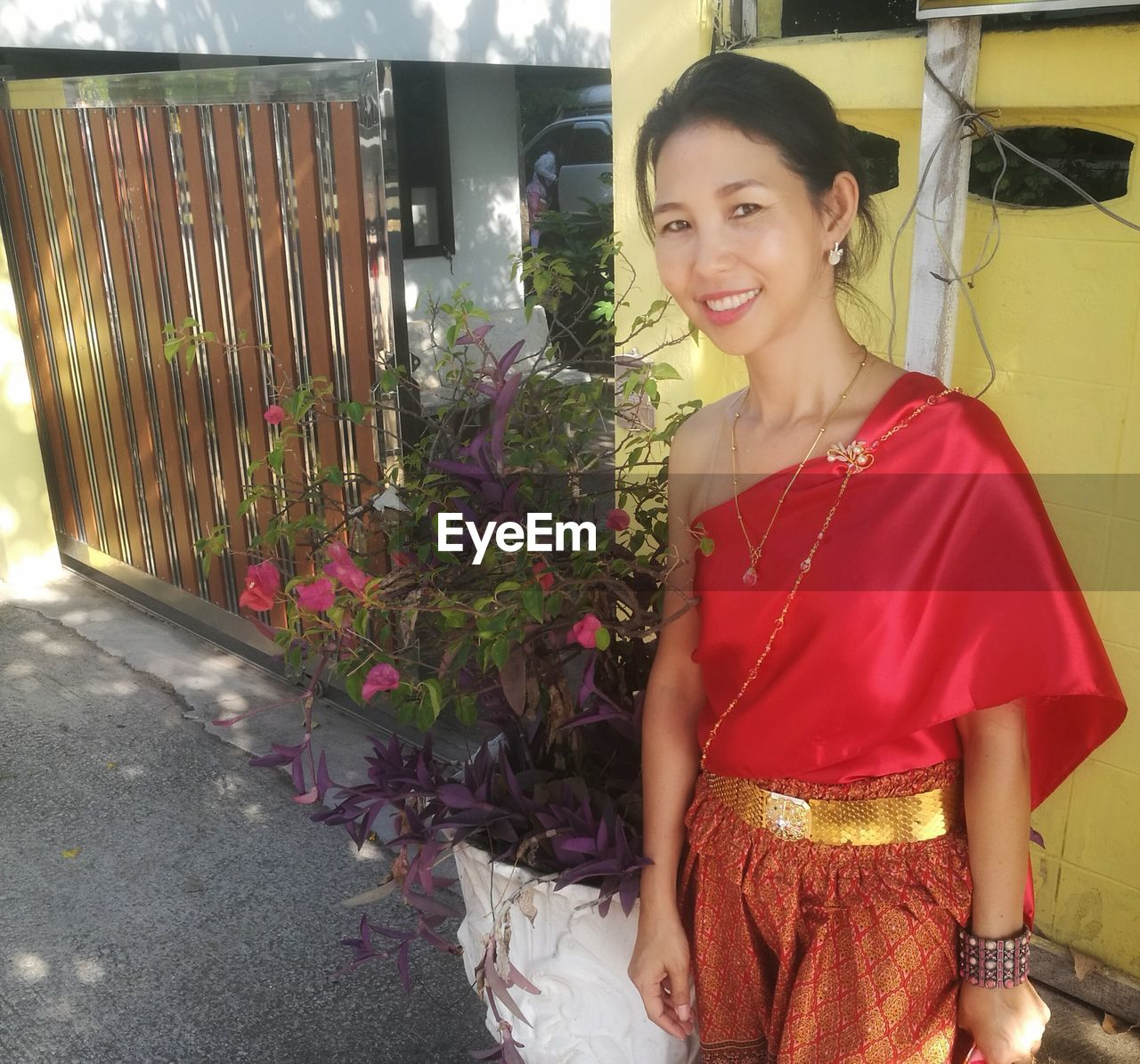 Portrait of smiling woman in traditional clothes while standing outdoors