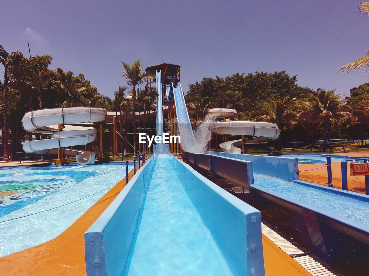 swimming pool, pool, water, tree, sky, nature, no people, blue, tropical climate, tourist resort, poolside, day, plant, palm tree, absence, clear sky, chair, water slide, water park, outdoors