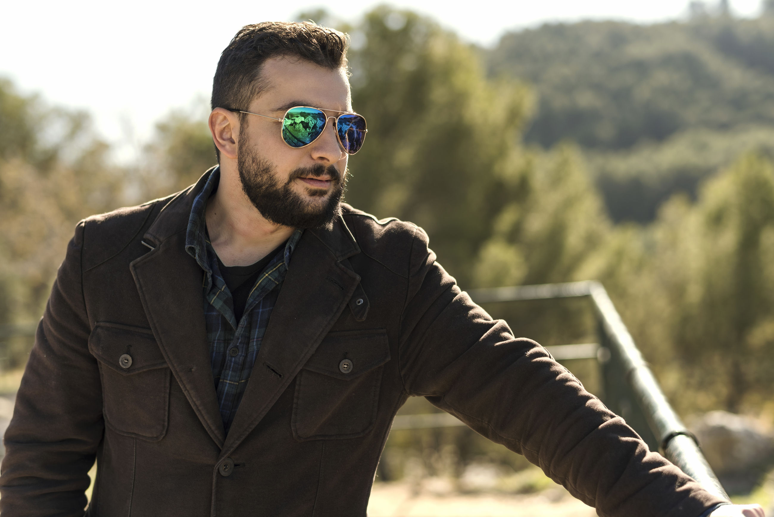 Bearded man wearing sunglasses while looking away during sunny day