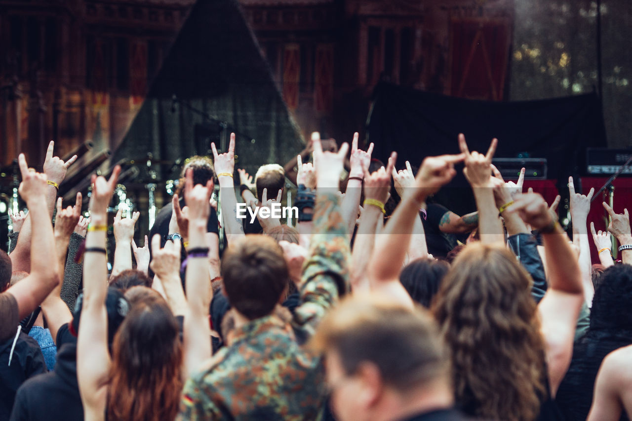 large group of people, real people, crowd, arms raised, togetherness, men, women, enjoyment, performance, day, outdoors, music, popular music concert, audience, excitement, protestor, photographing, human hand, adult, people