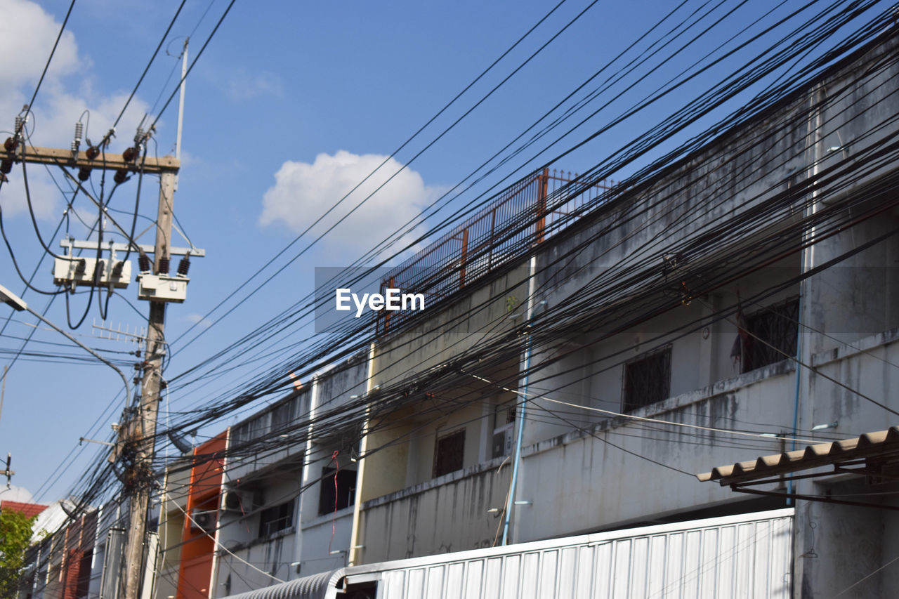 architecture, built structure, building exterior, cable, electricity, sky, power line, building, technology, connection, low angle view, no people, nature, day, power supply, outdoors, fuel and power generation, residential district, city, window, complexity, telephone line