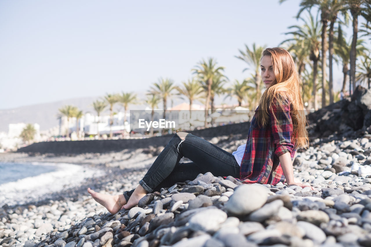 Woman sitting on pebbles against clear sky
