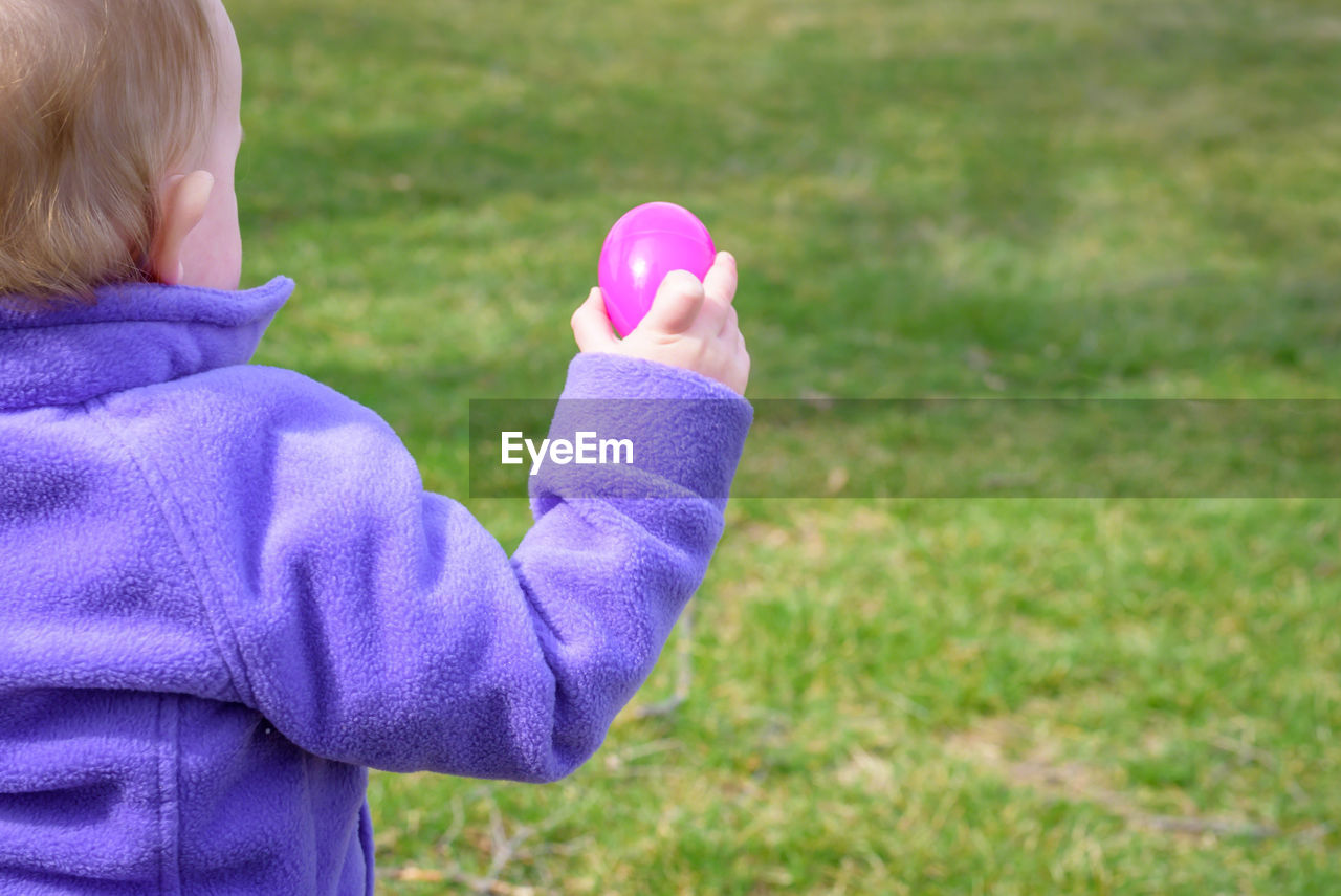 Close-up of boy holding easter egg on field