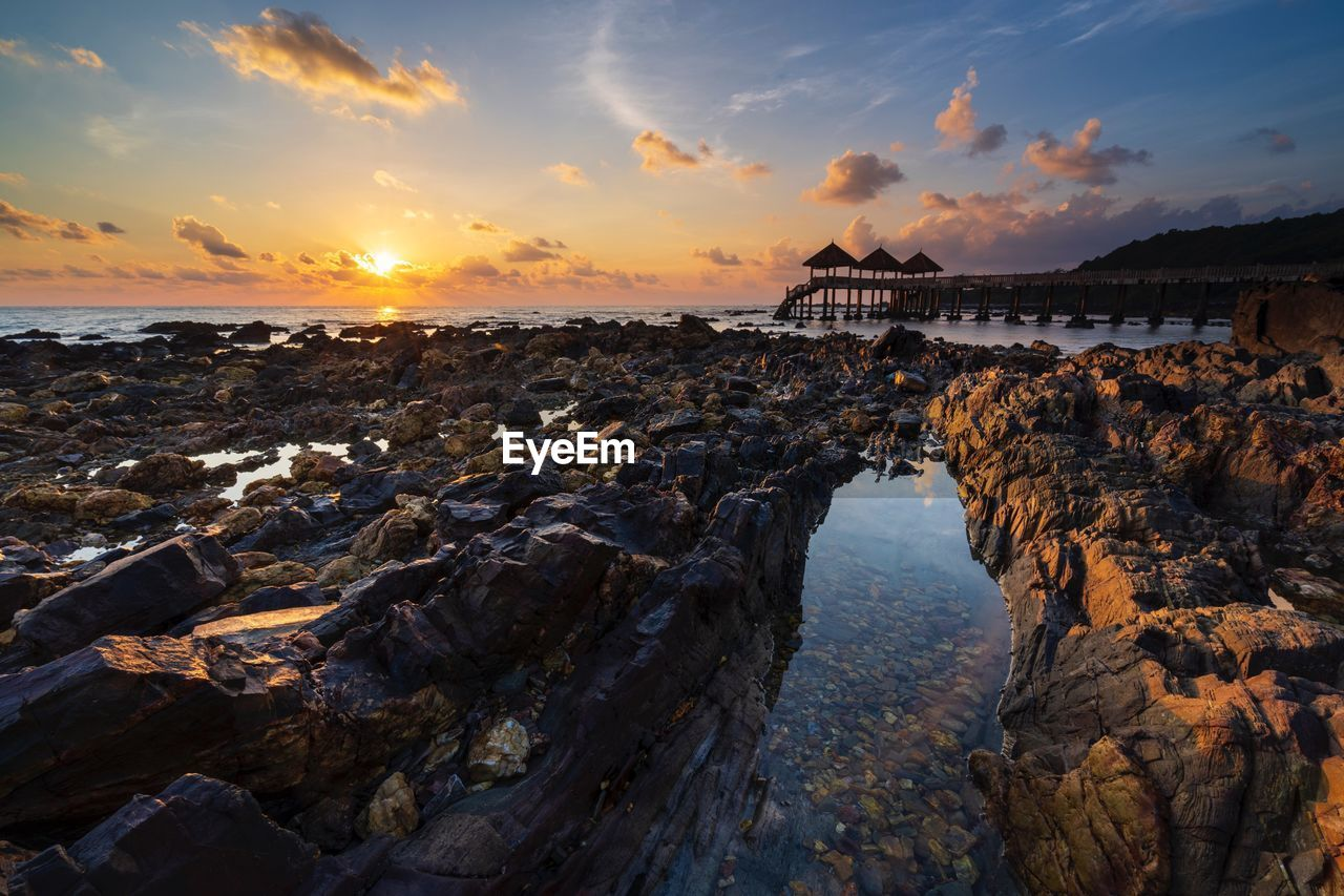 sky, water, sunset, cloud - sky, scenics - nature, rock, sea, beauty in nature, beach, rock - object, nature, land, tranquil scene, solid, built structure, tranquility, architecture, orange color, no people, horizon over water, outdoors