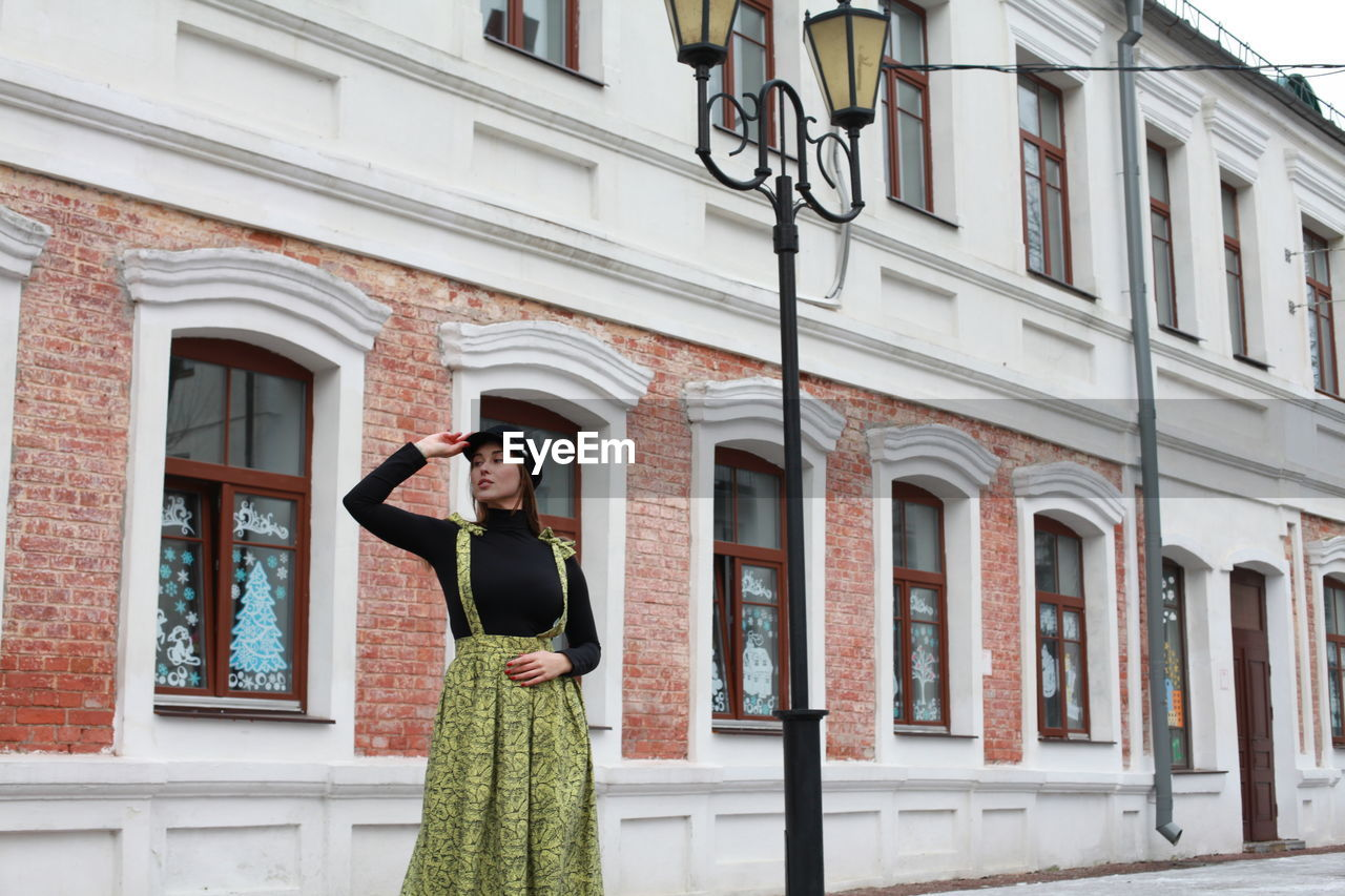 Woman standing against building