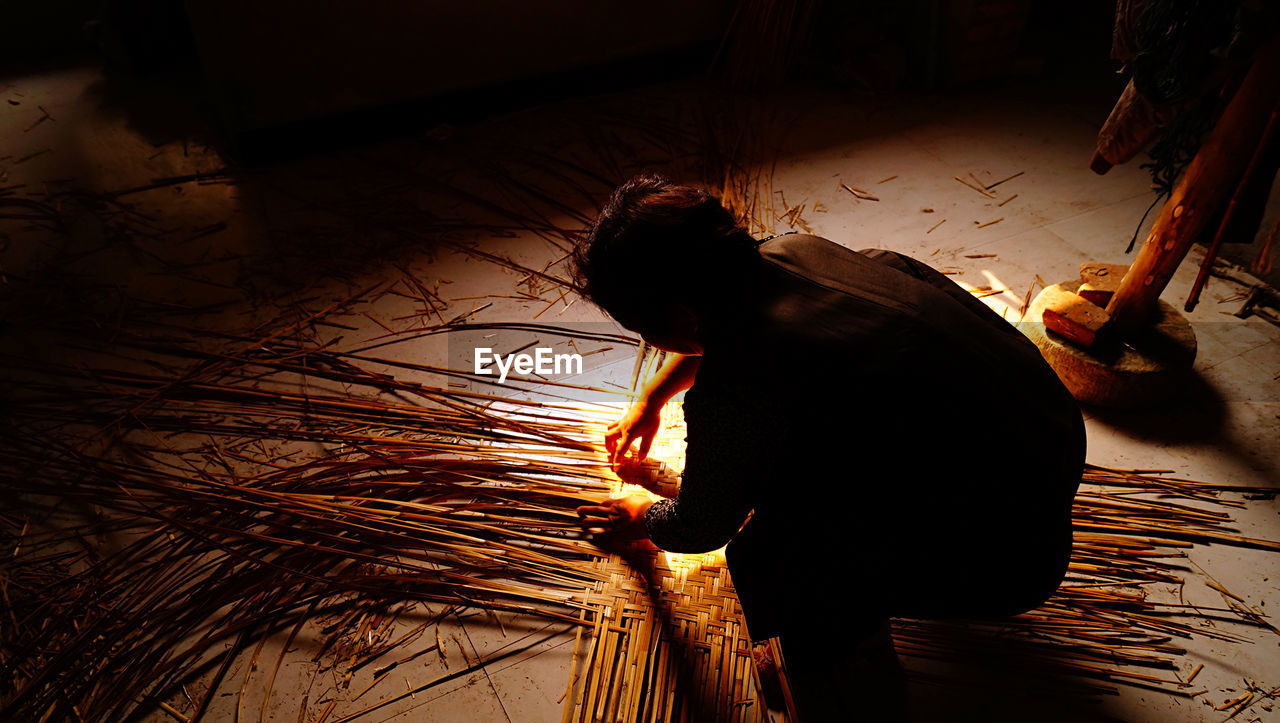 High Angle View Of Worker Making Thatched Roof