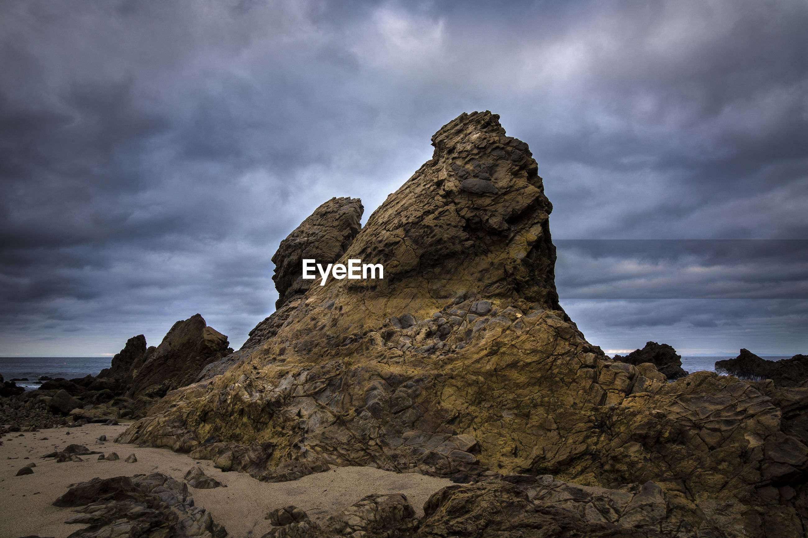 Rock formation at beach against cloudy sky