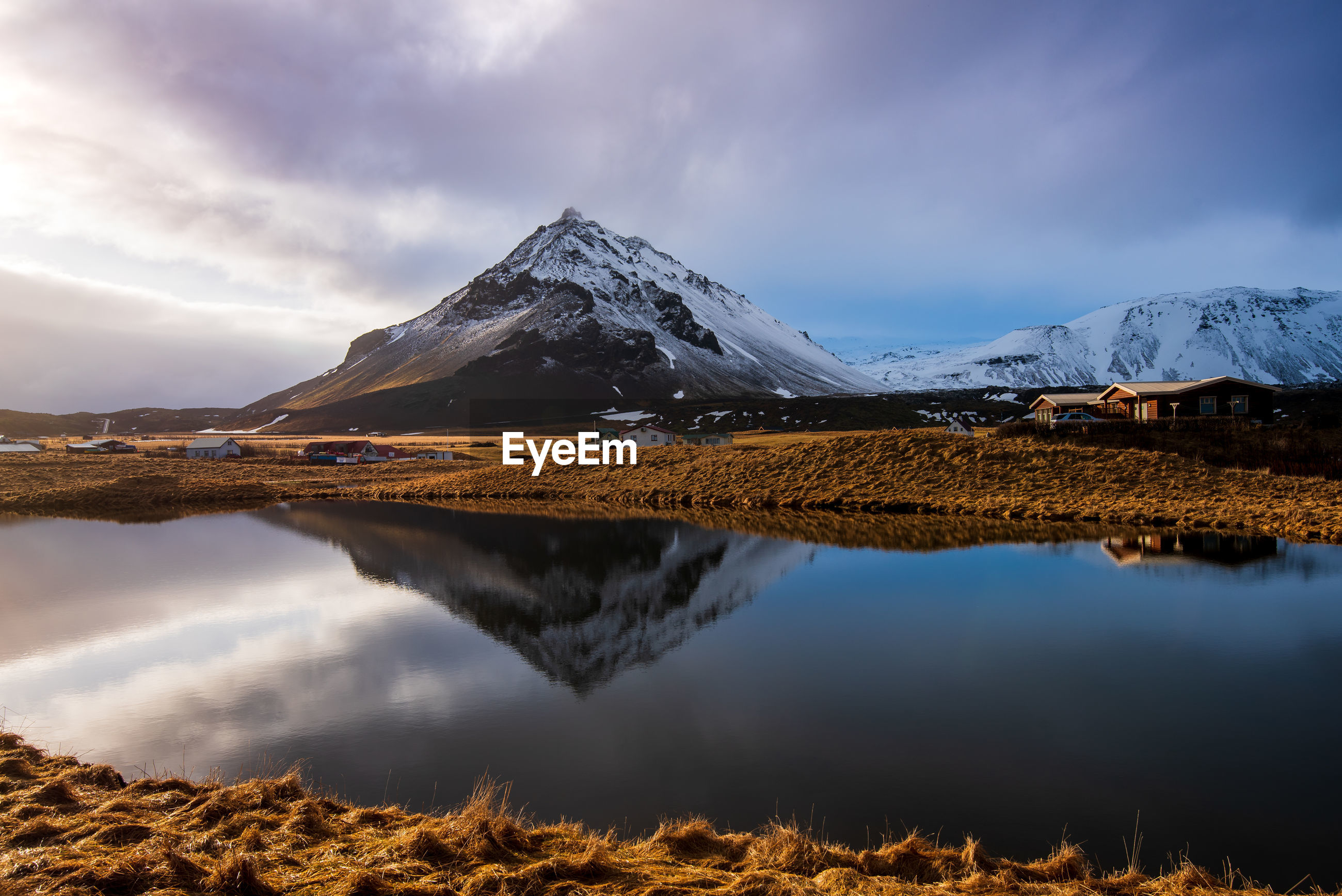 Icelandic dramatic landscape with lake and stapafell mountains covered in snow in iceland