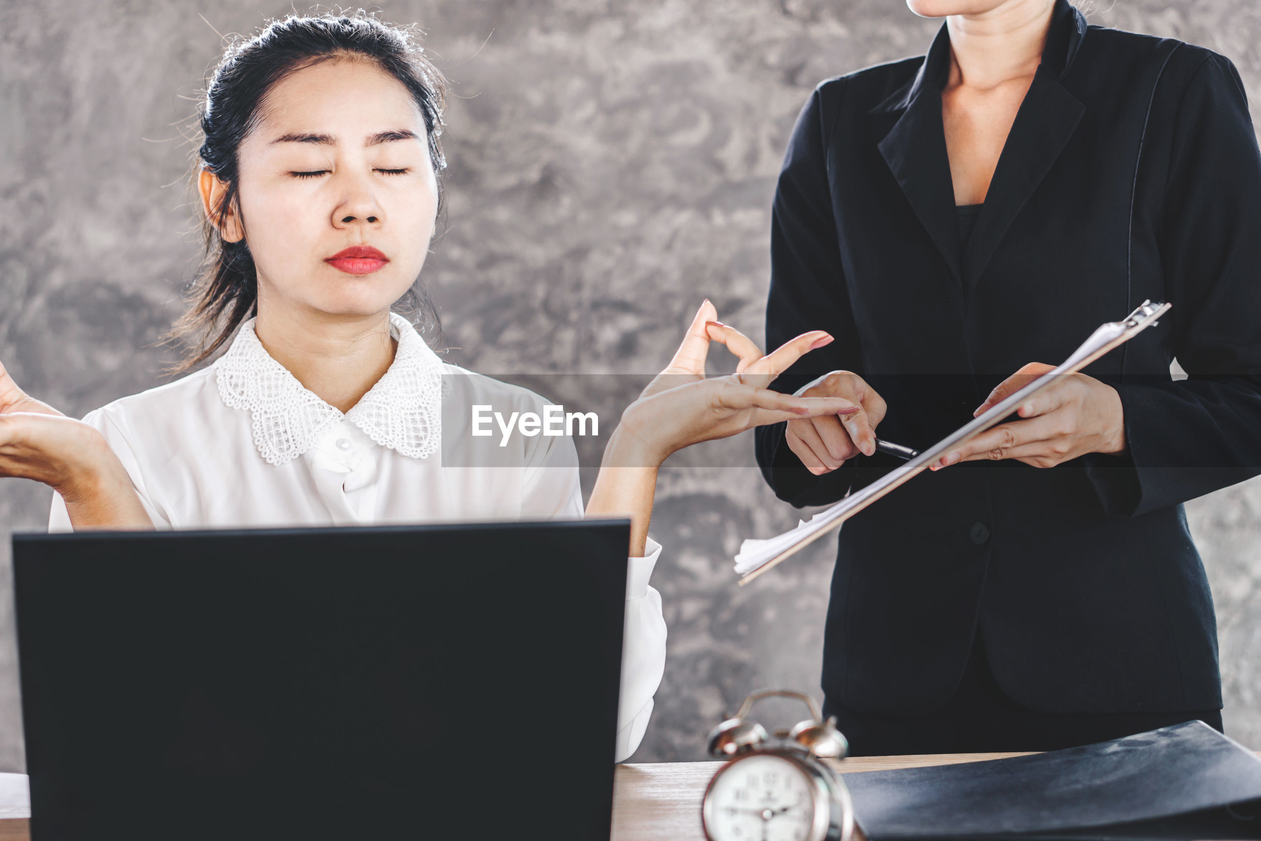 Businesswoman gesturing while boss holding document