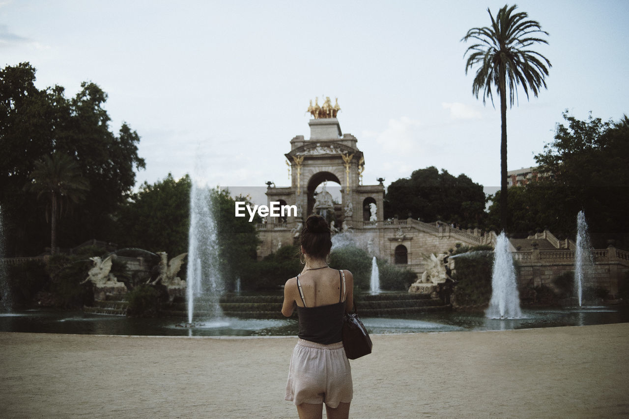 Rear View Of Woman Standing Fountain Against Sky