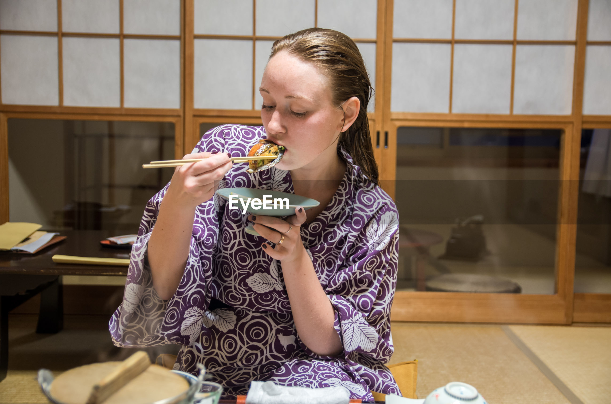 Young woman eating japanese food