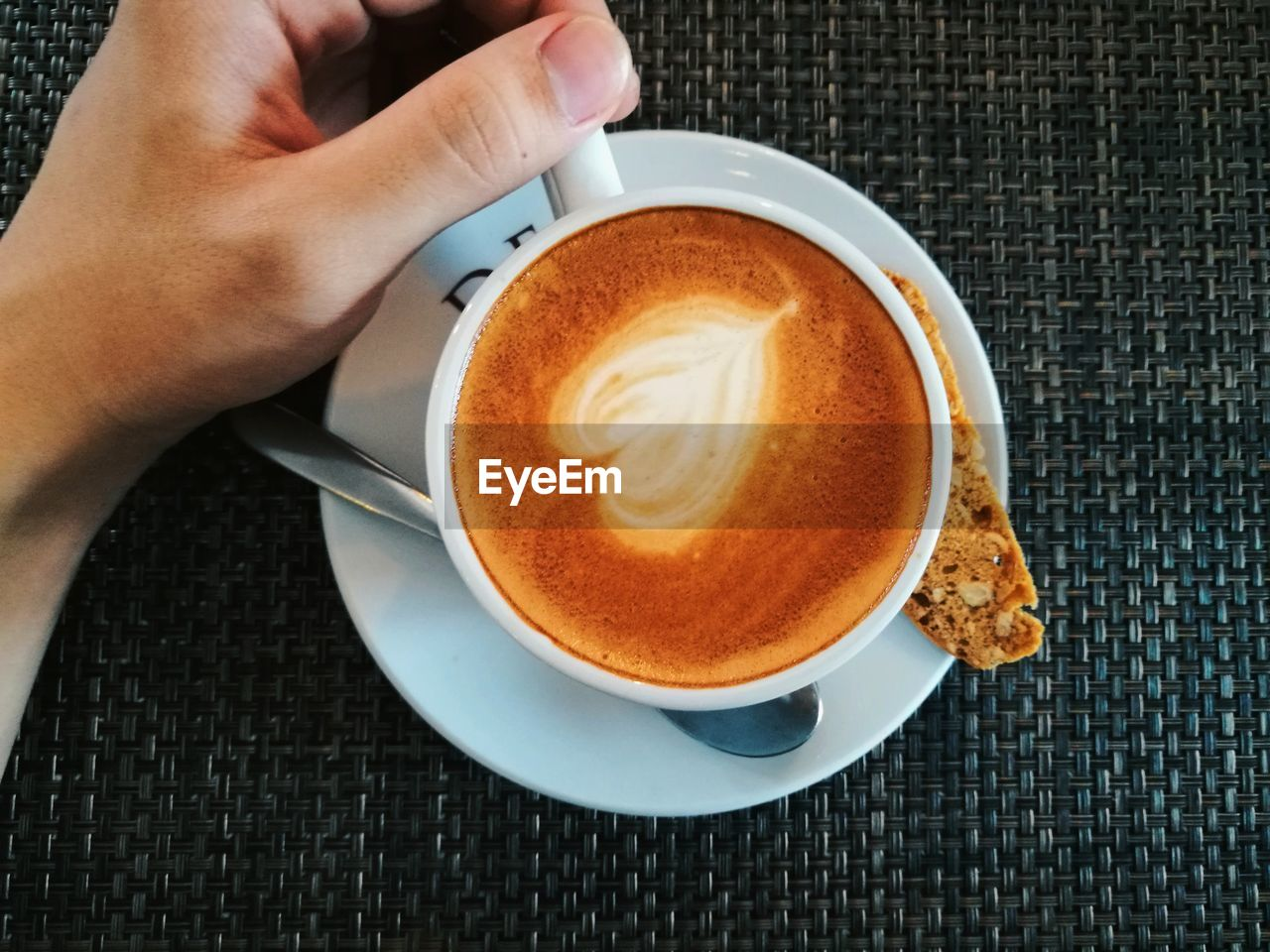 coffee cup, refreshment, food and drink, drink, coffee - drink, human hand, table, one person, saucer, indoors, high angle view, freshness, human body part, close-up, frothy drink, real people, holding, froth art, food, cappuccino, day, people