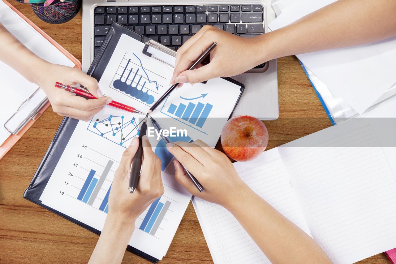 Cropped hands of colleagues working over graph in office