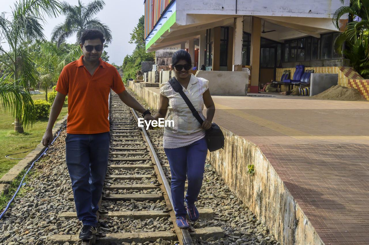 Couple walking on railroad track