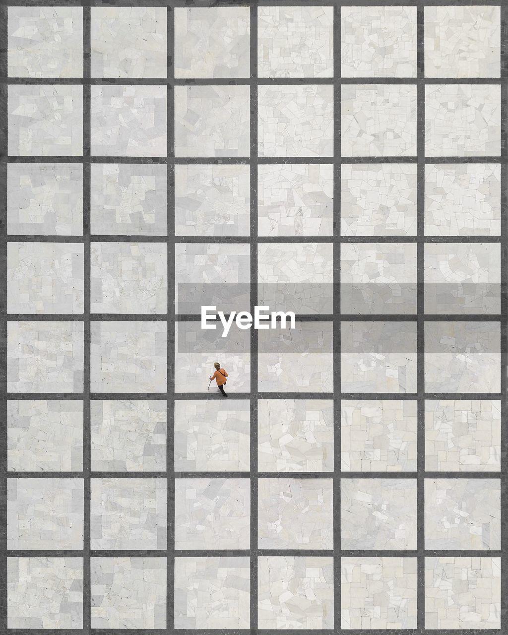 Aerial View Of Woman Walking On Tiled Floor