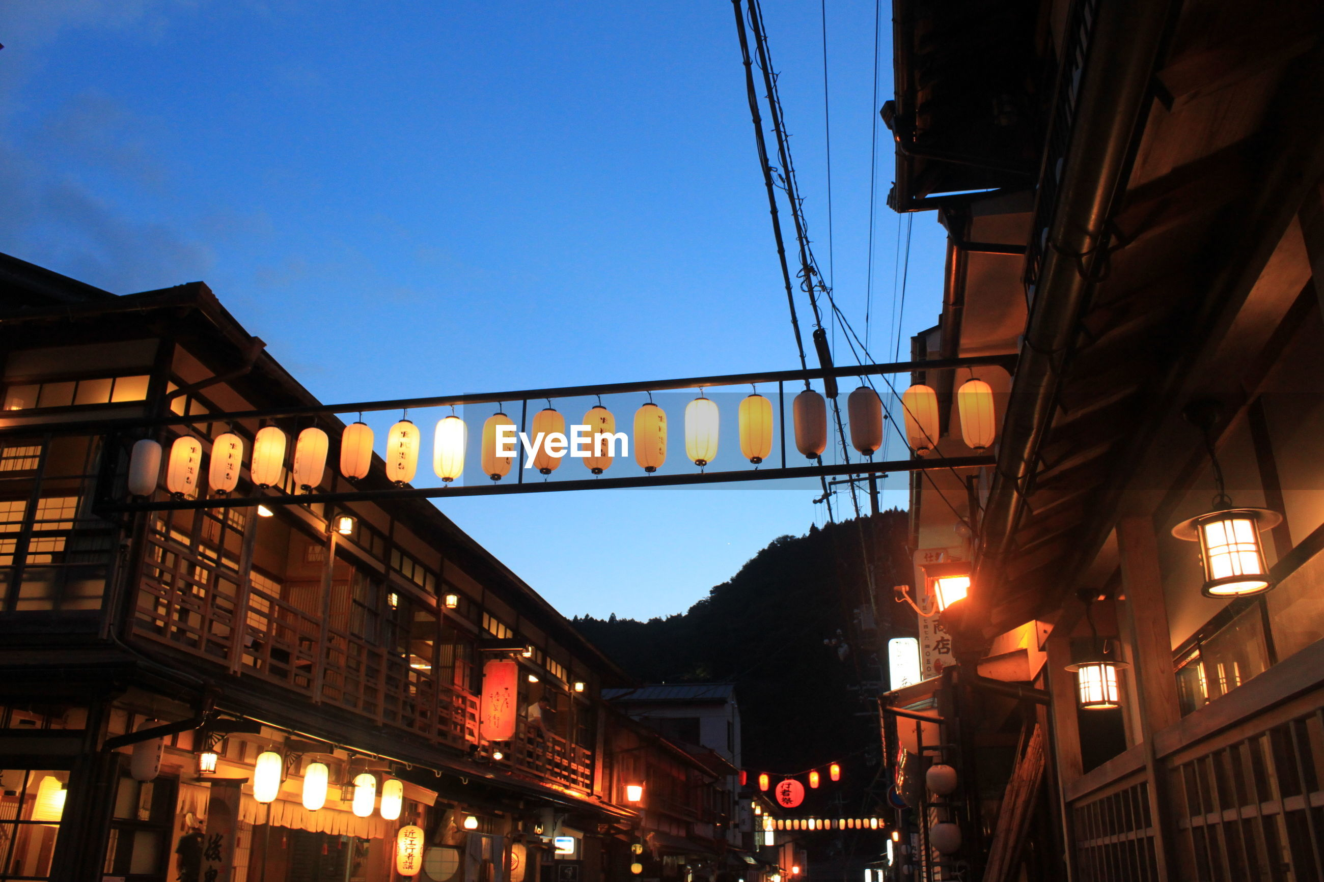 Illuminated chinese lanterns connecting houses against sky