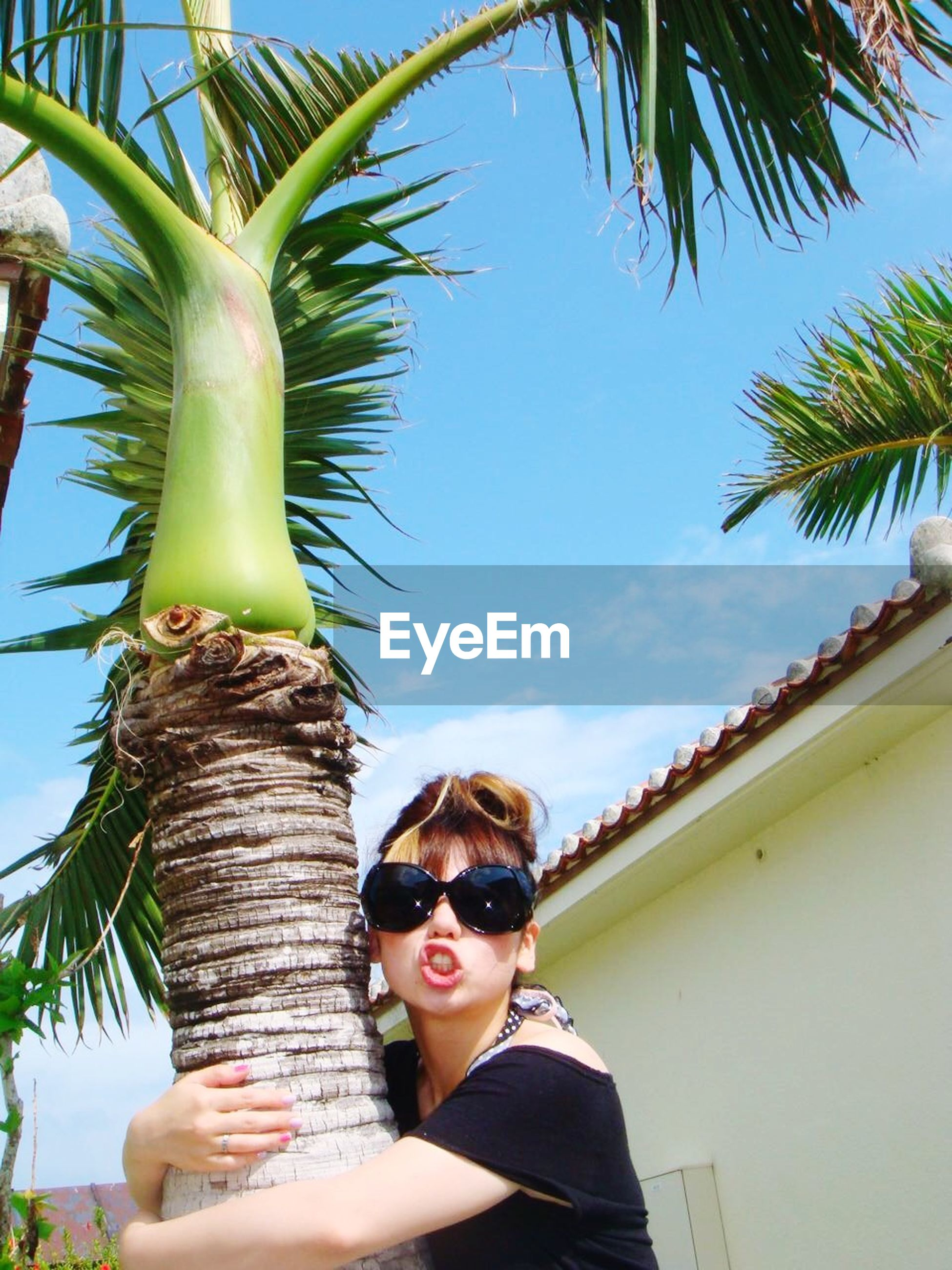 young adult, palm tree, lifestyles, person, leisure activity, looking at camera, portrait, front view, young women, tree, sky, sunglasses, low angle view, casual clothing, smiling, sunlight, headshot