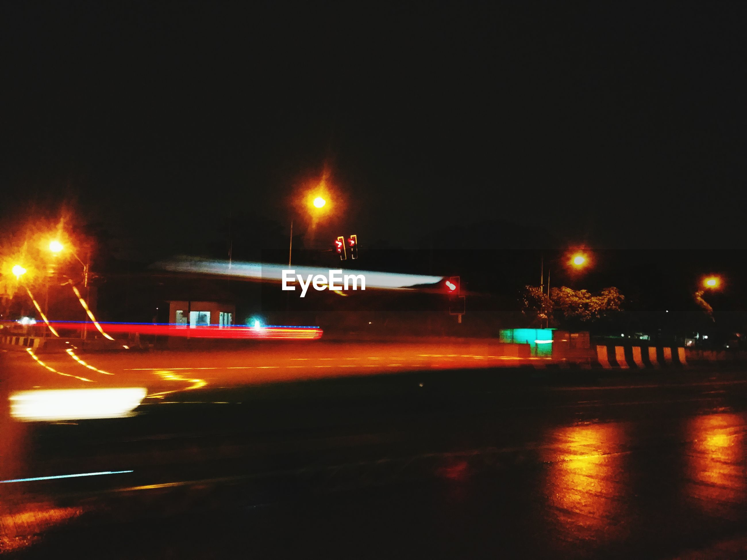LIGHT TRAILS ON ROAD IN CITY AGAINST CLEAR SKY